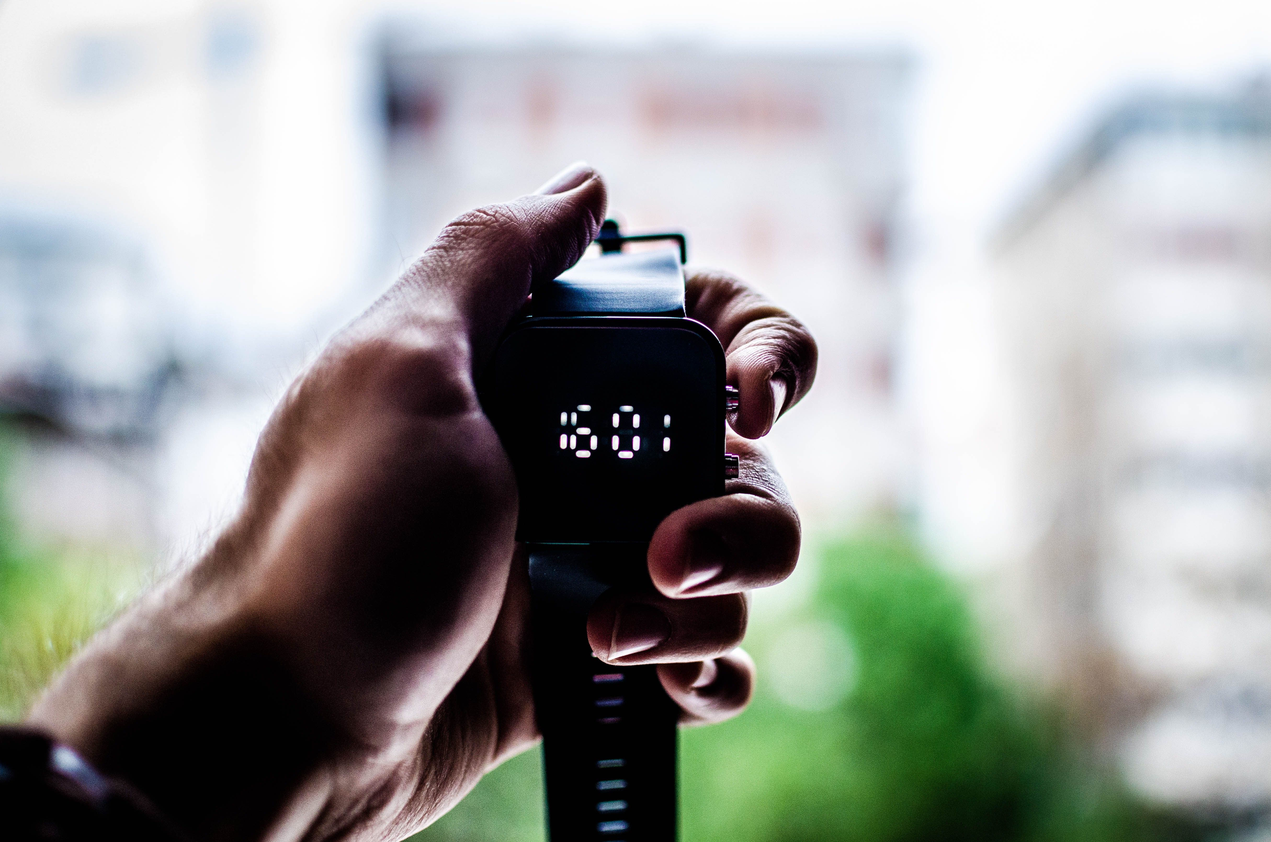 A person's hand holding a digital watch displaying the time