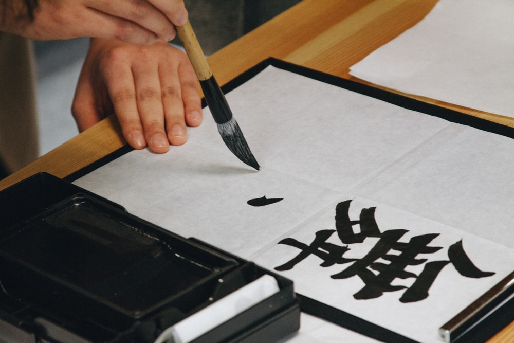 A close-up of a person practicing brush calligraphy.