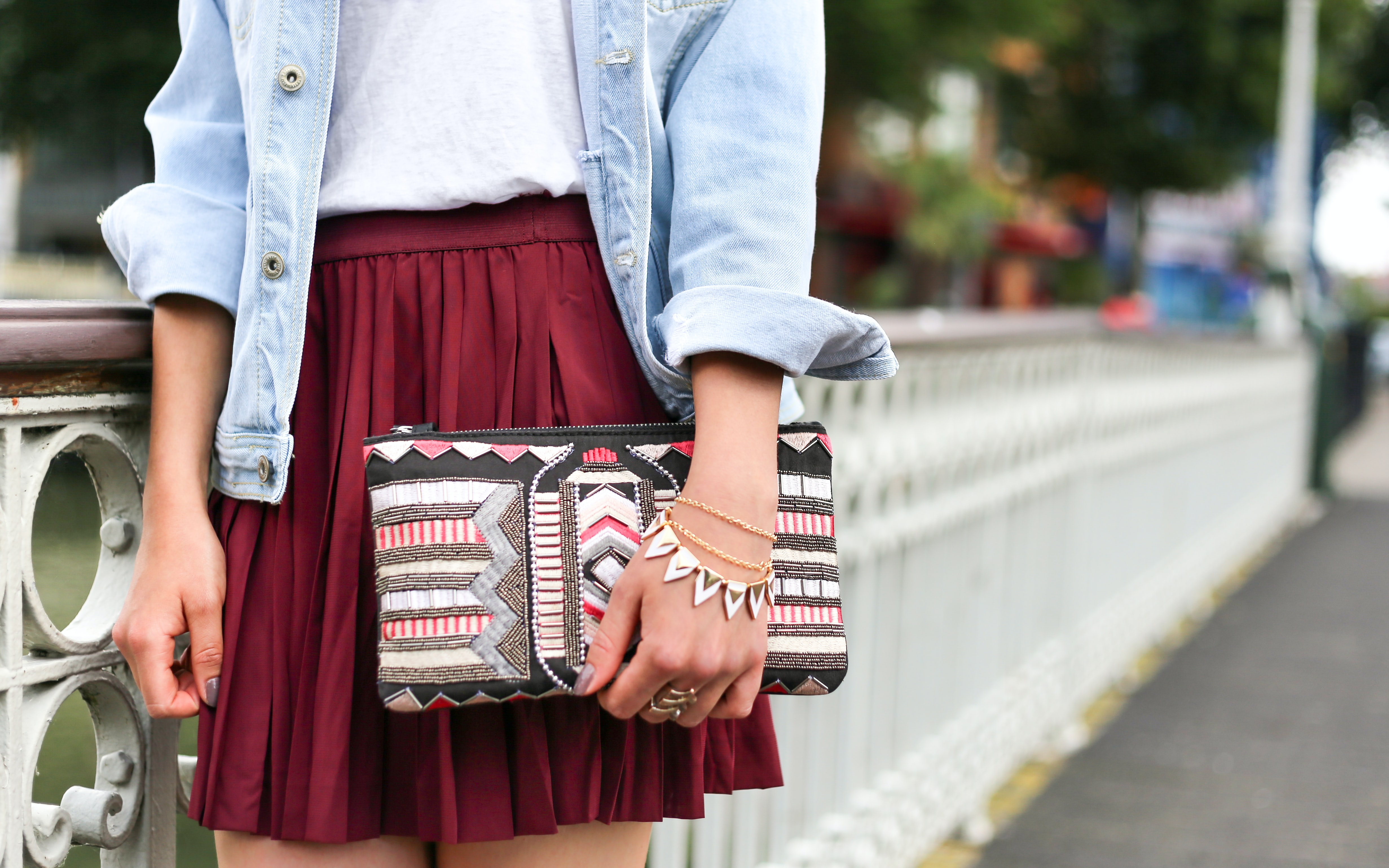 A woman in a red skirt, jean shirt, and jewelry holds a patterned clutch in Rotterdam