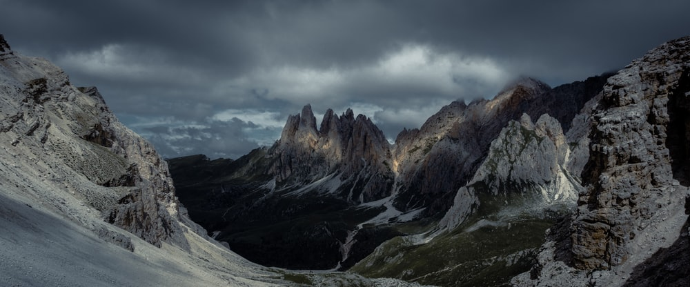 beige mountain under cloudy sky