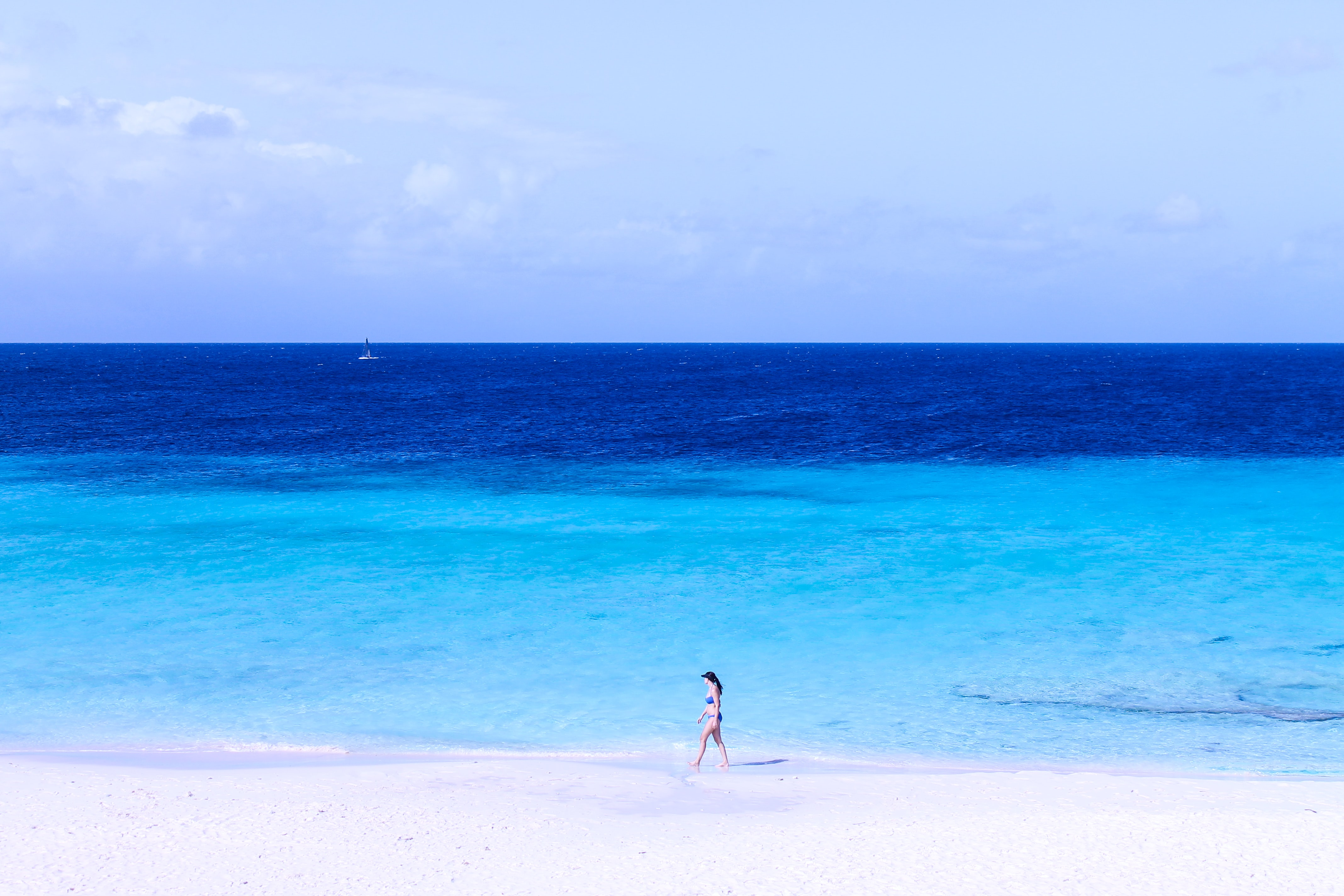 A lone woman in a swimsuit walking on the edge of a beach with deep blue sea stretching to the horizon