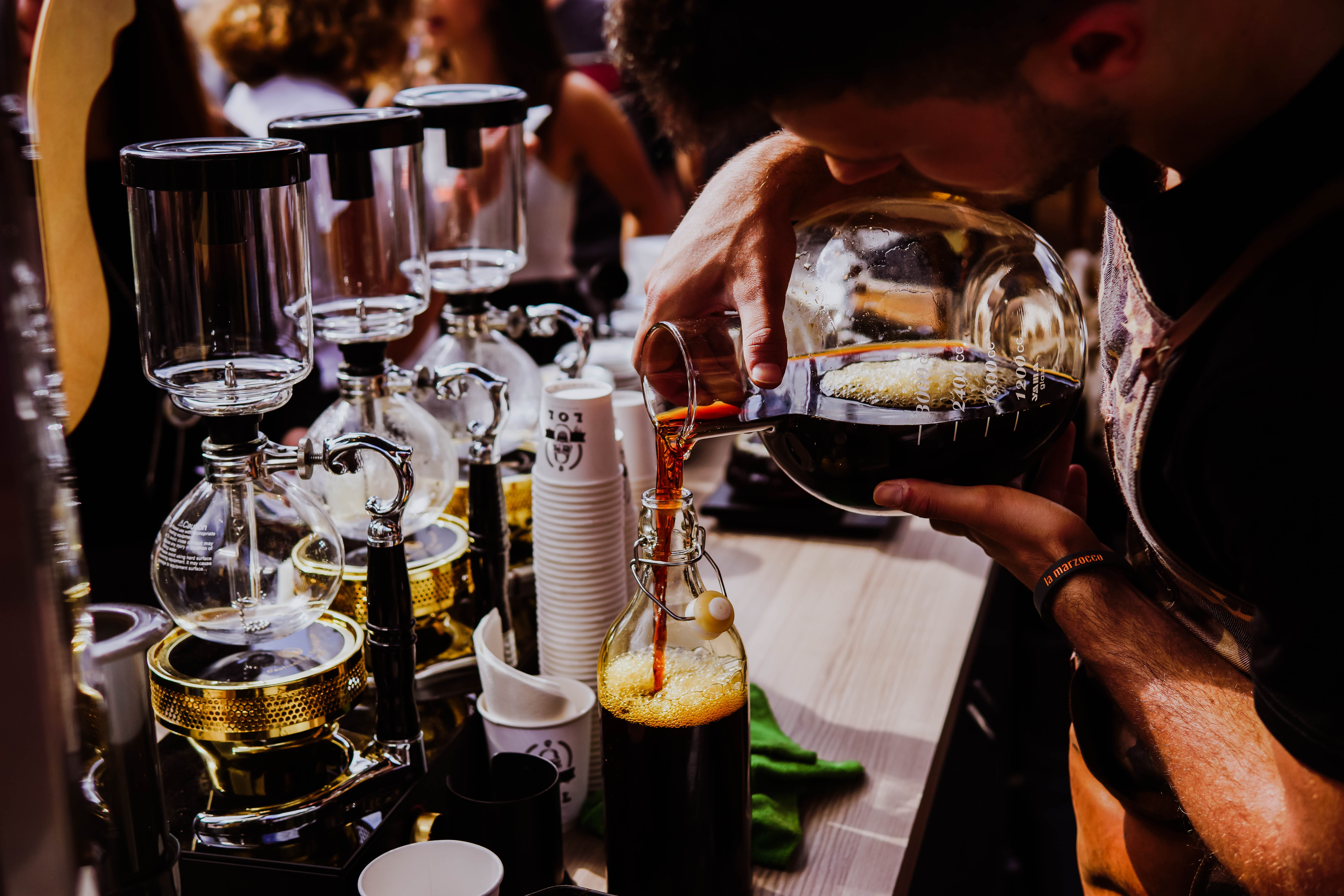 A barista pouring coffee from a jug into a bottle