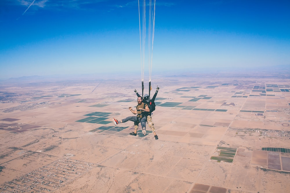 two men in 1 parachute in mid air during daytime