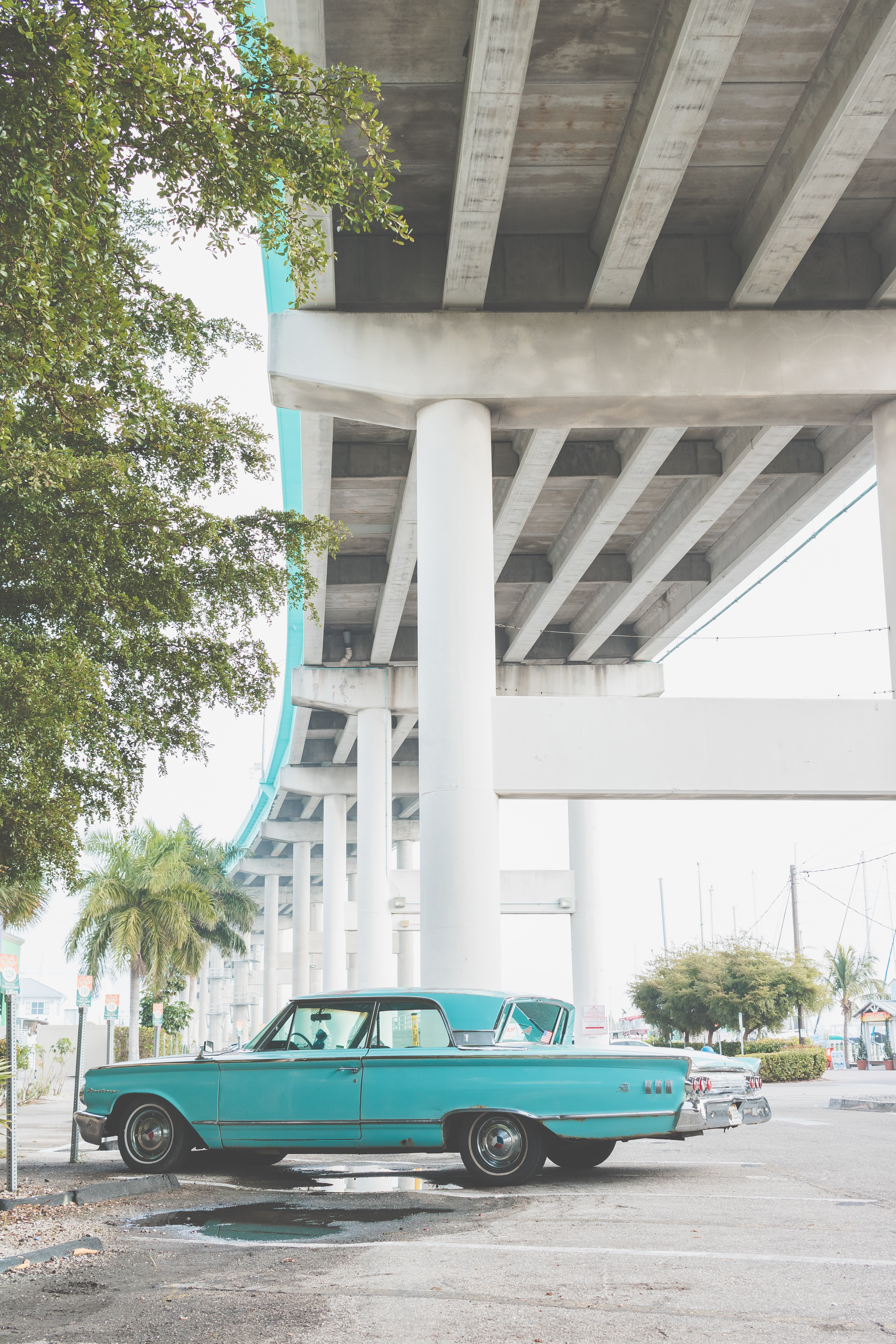 Vintage turquoise car parked underneath an overpass.