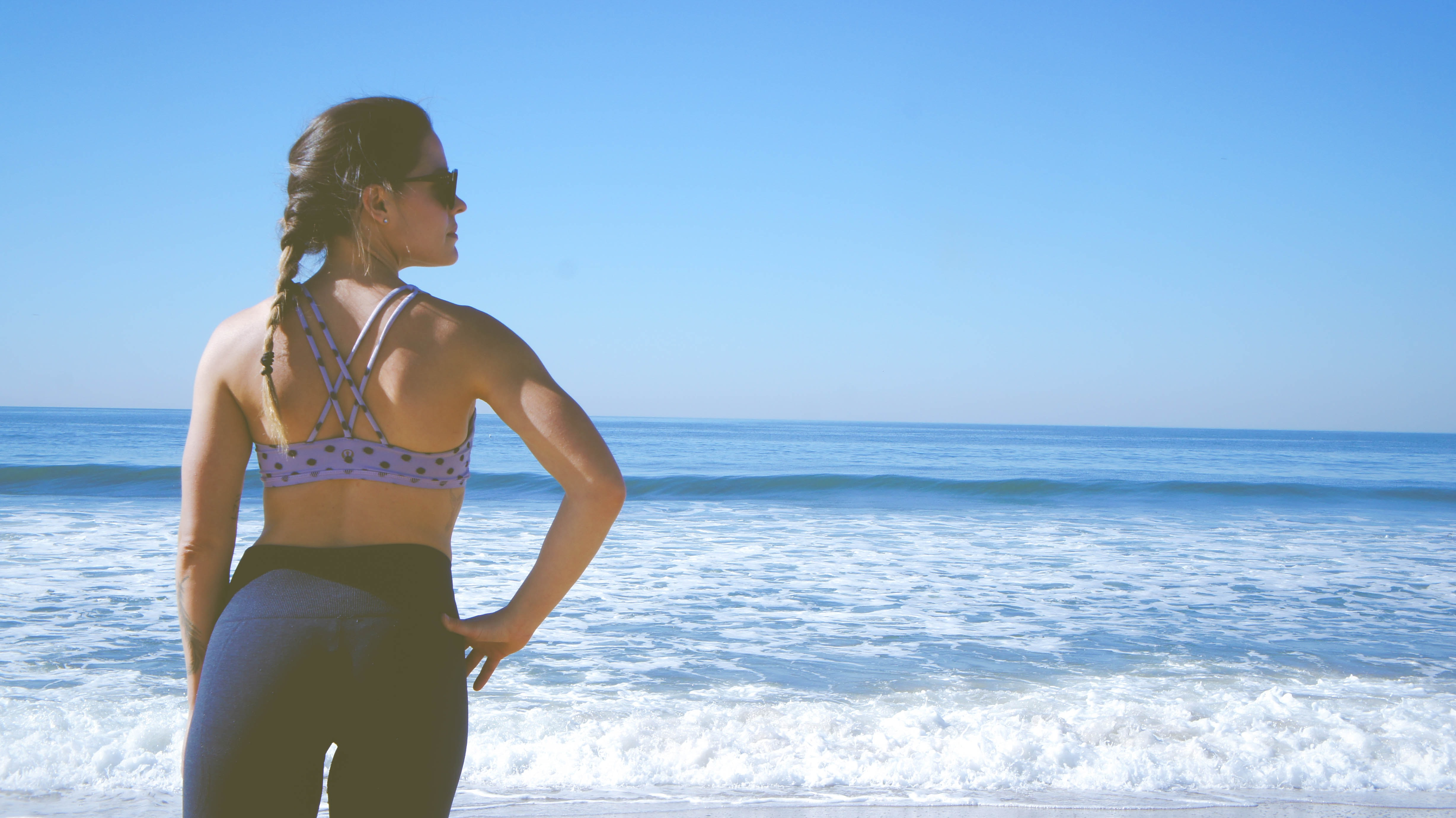 A woman wearing leggings, a sports bra, and sunglasses with a braid in her hair in Manhattan Beach