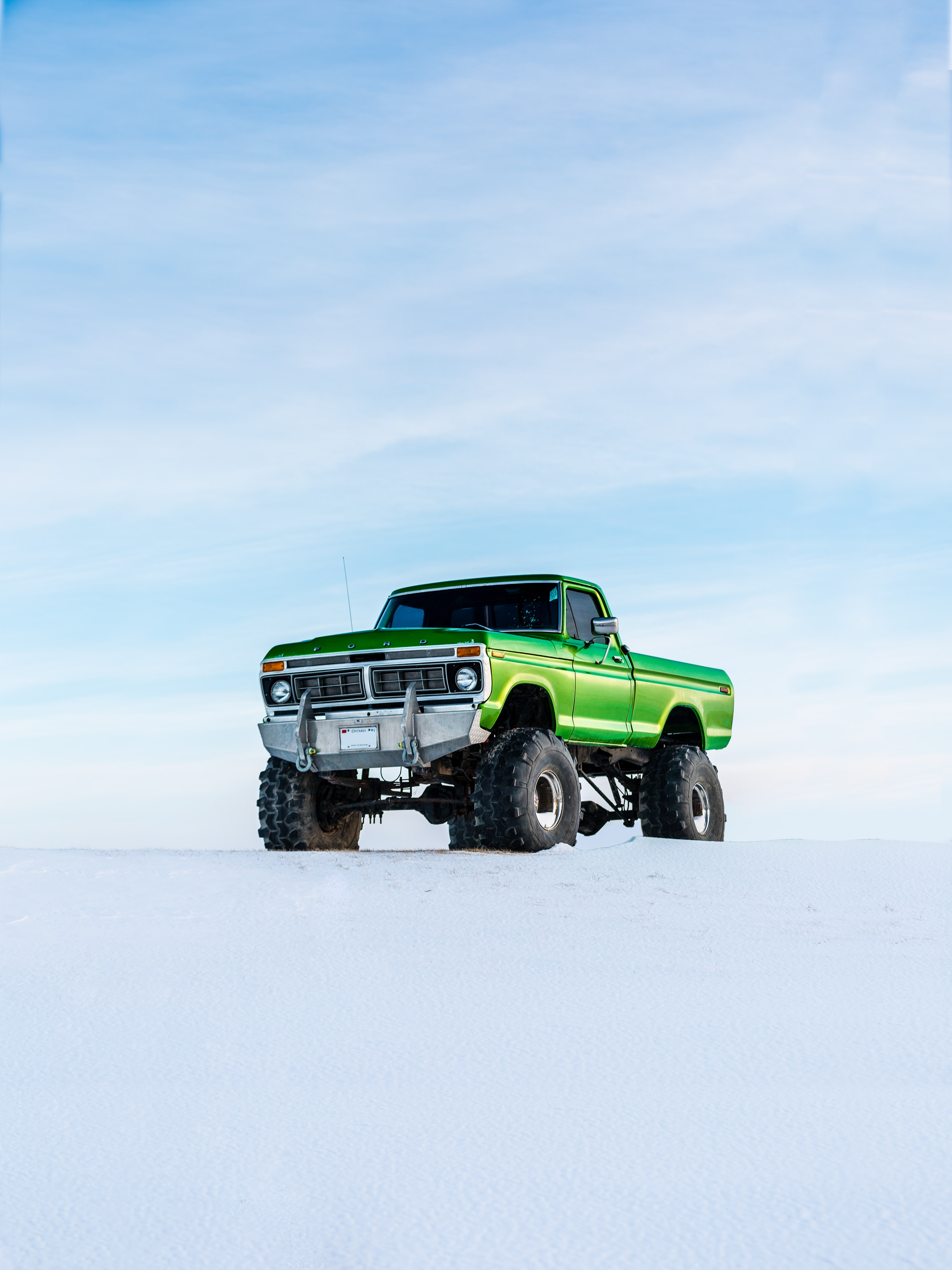 A large green truck parked in the snow in Elora