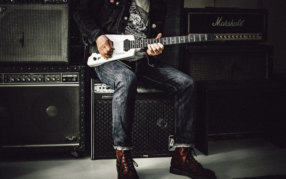 man wearing blue denim jeans playing white and black electric guitar sitting on black guitar amplifier