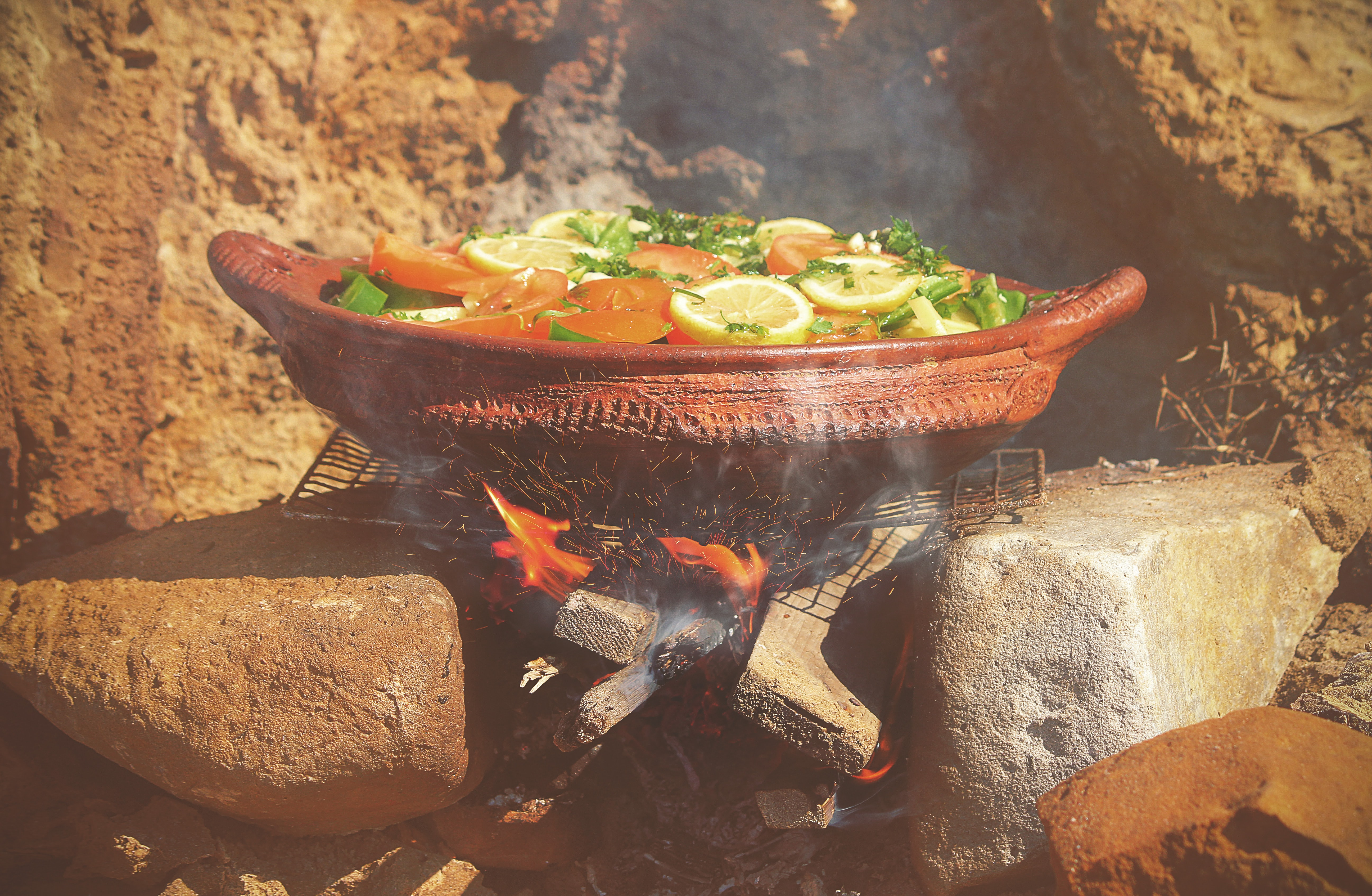 Moroccan dish with lemons and vegetables cooking over hot coals