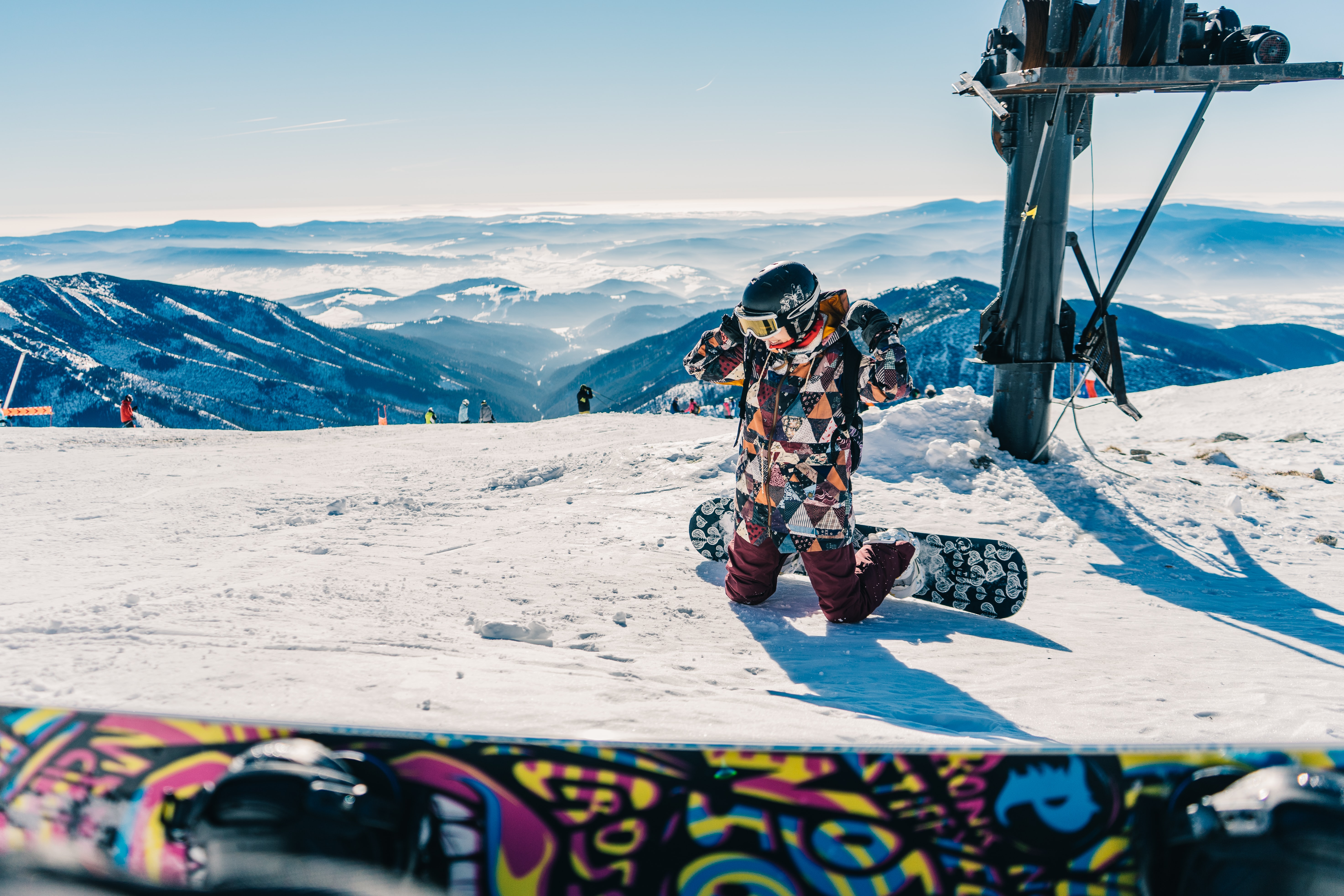 A warmly dressed snowboarder with a colorful snowboard at a Jasna snow hill