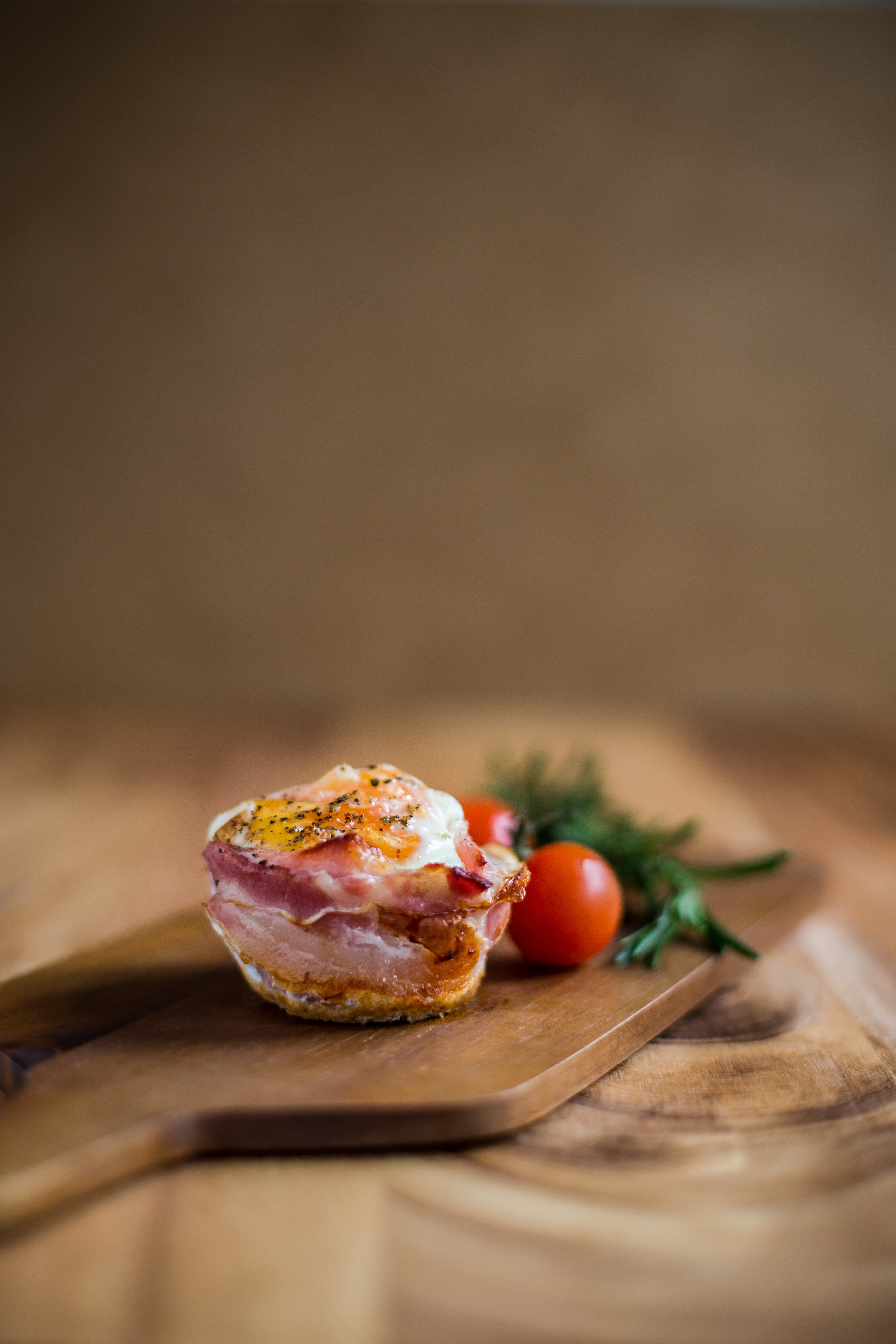 selective focus photography of cooked food near tomatoes both on brown wooden chopping board
