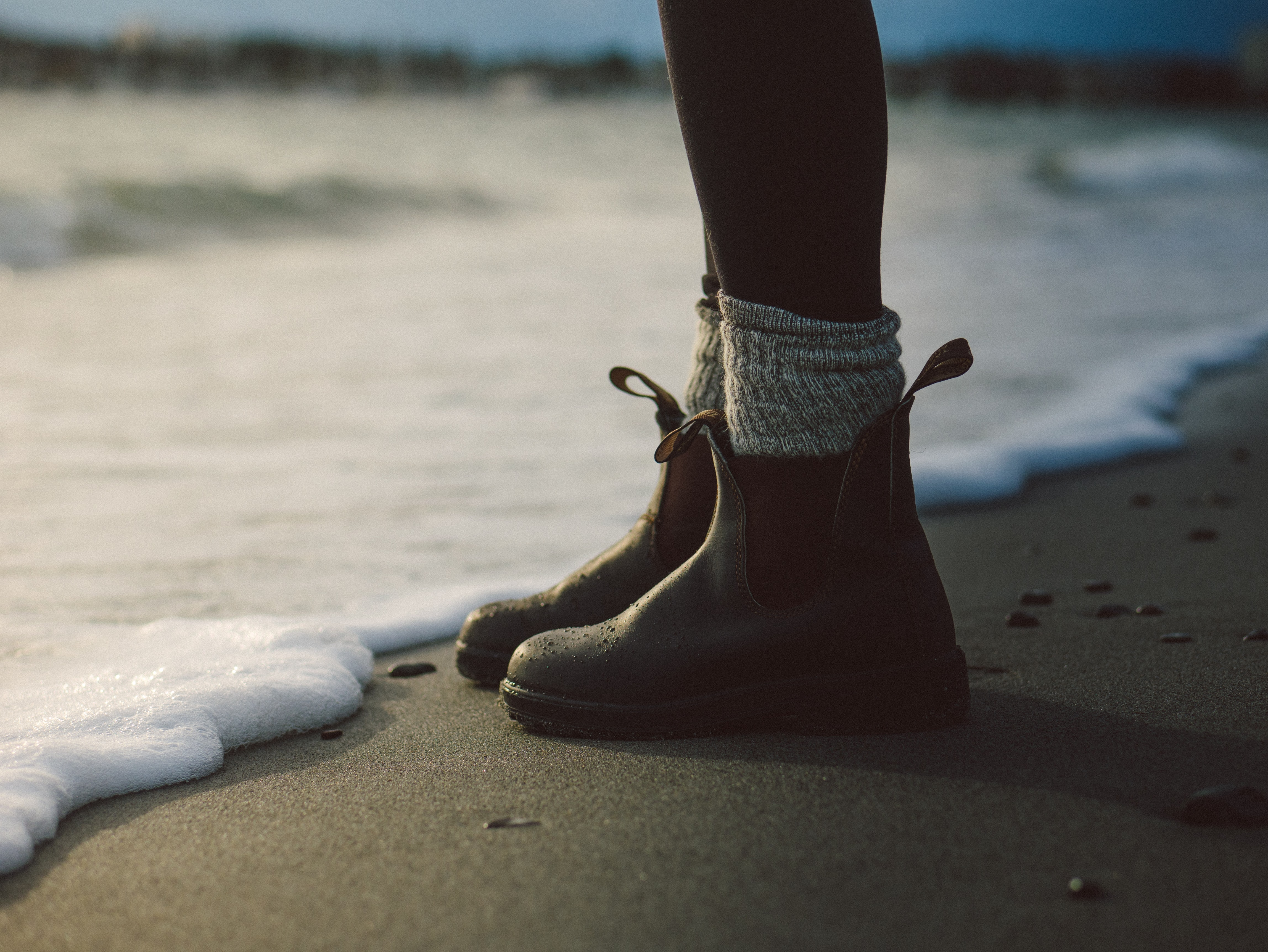 A person in boots stands on the sand near the shore as the water's foam movies in