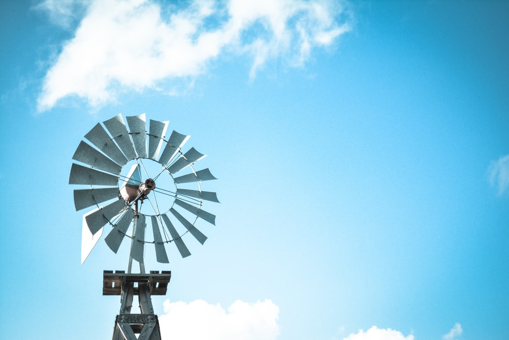 windmill under blue and white cloudy skies at daytime