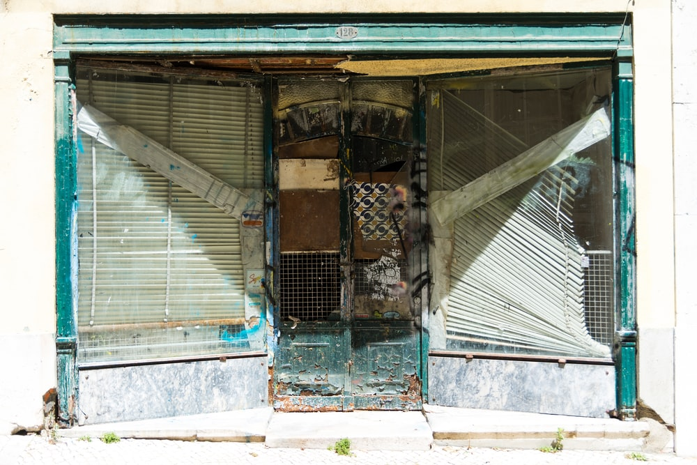 abandoned building with white venetian blinds on window