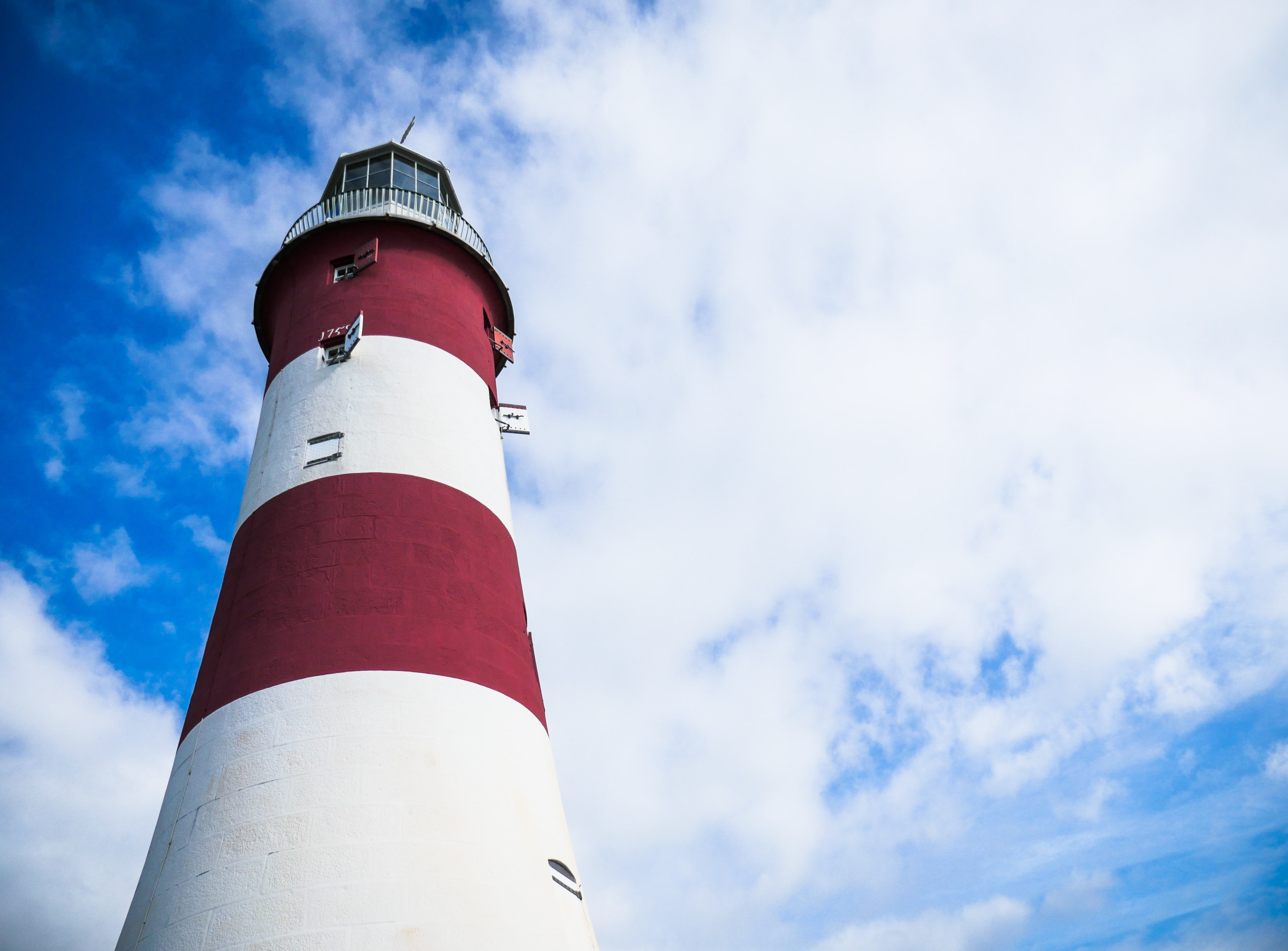 red and white lighthouse under cloudy blue sky
