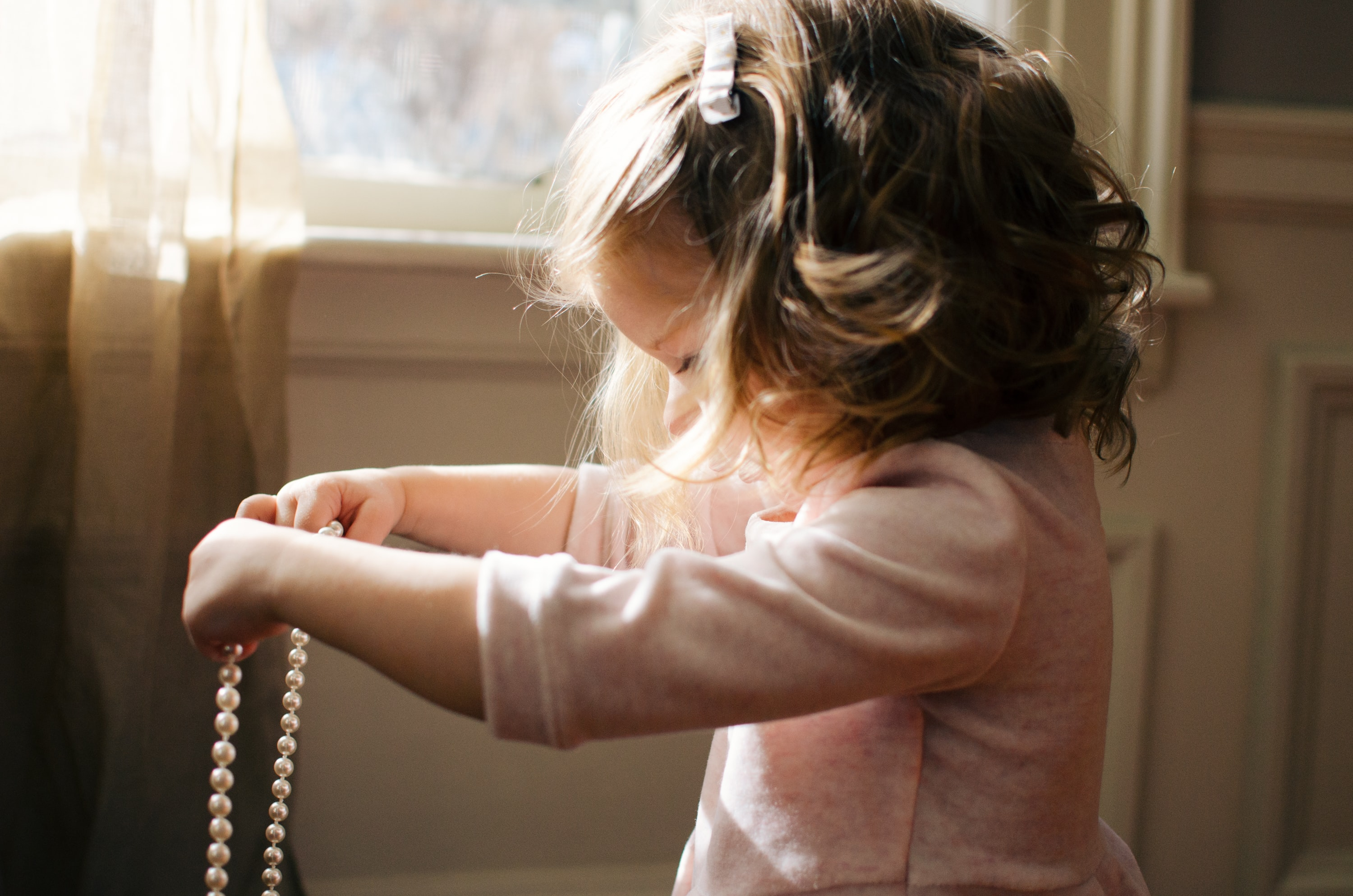 Young girl with a pink shirt holder her mother's pearl necklace