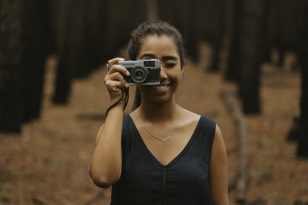 woman holding silver DSLR camera during daytime