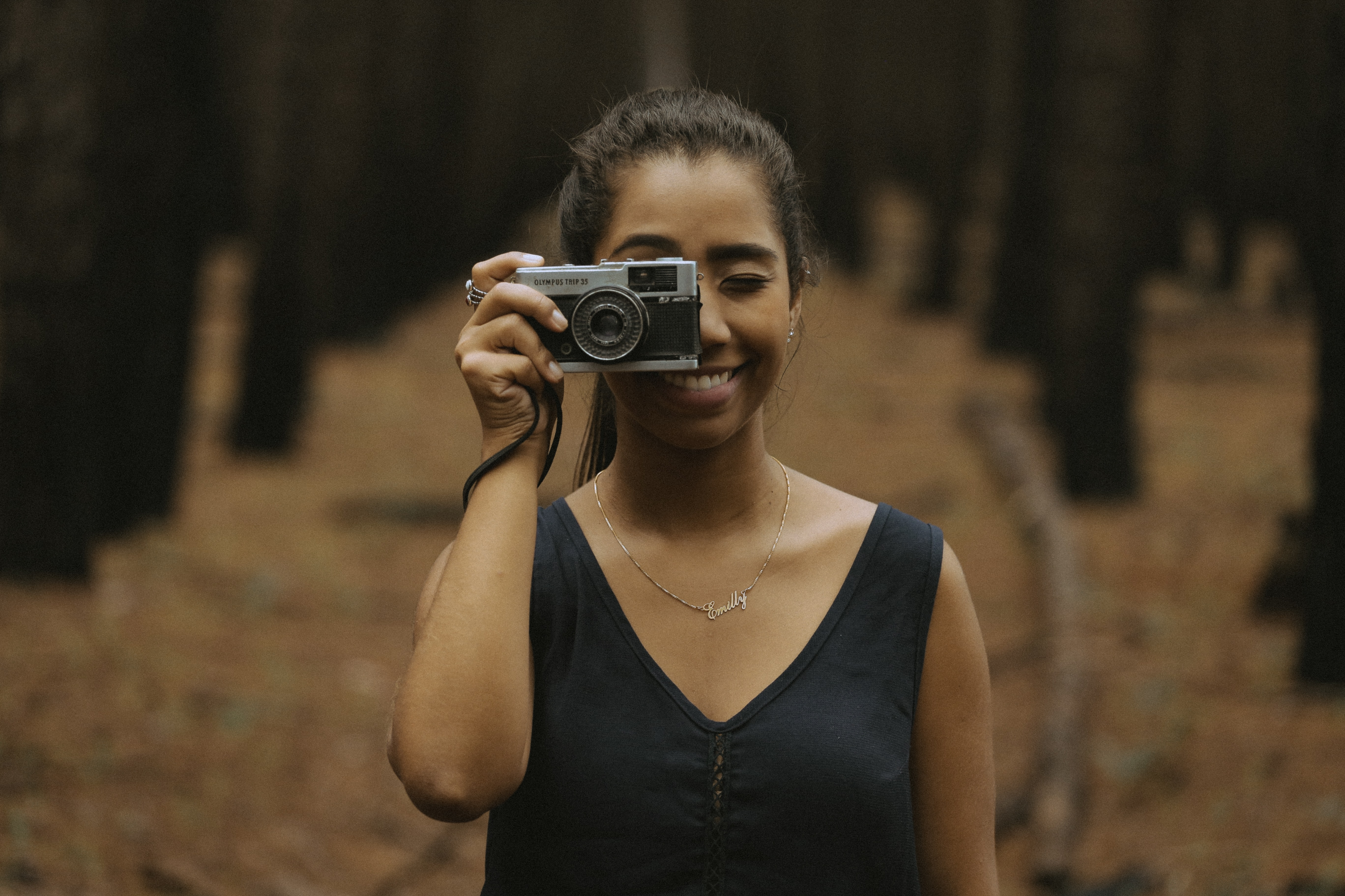 A smiling young woman taking a photo with a vintage camera