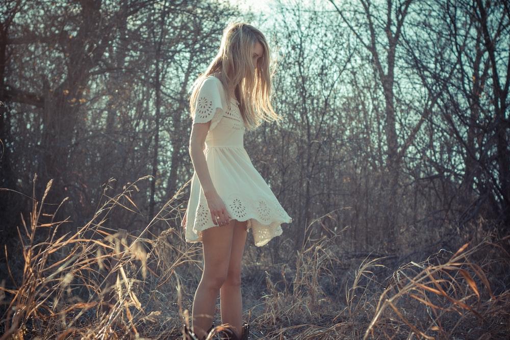 woman wearing dress standing on plant field near bare trees