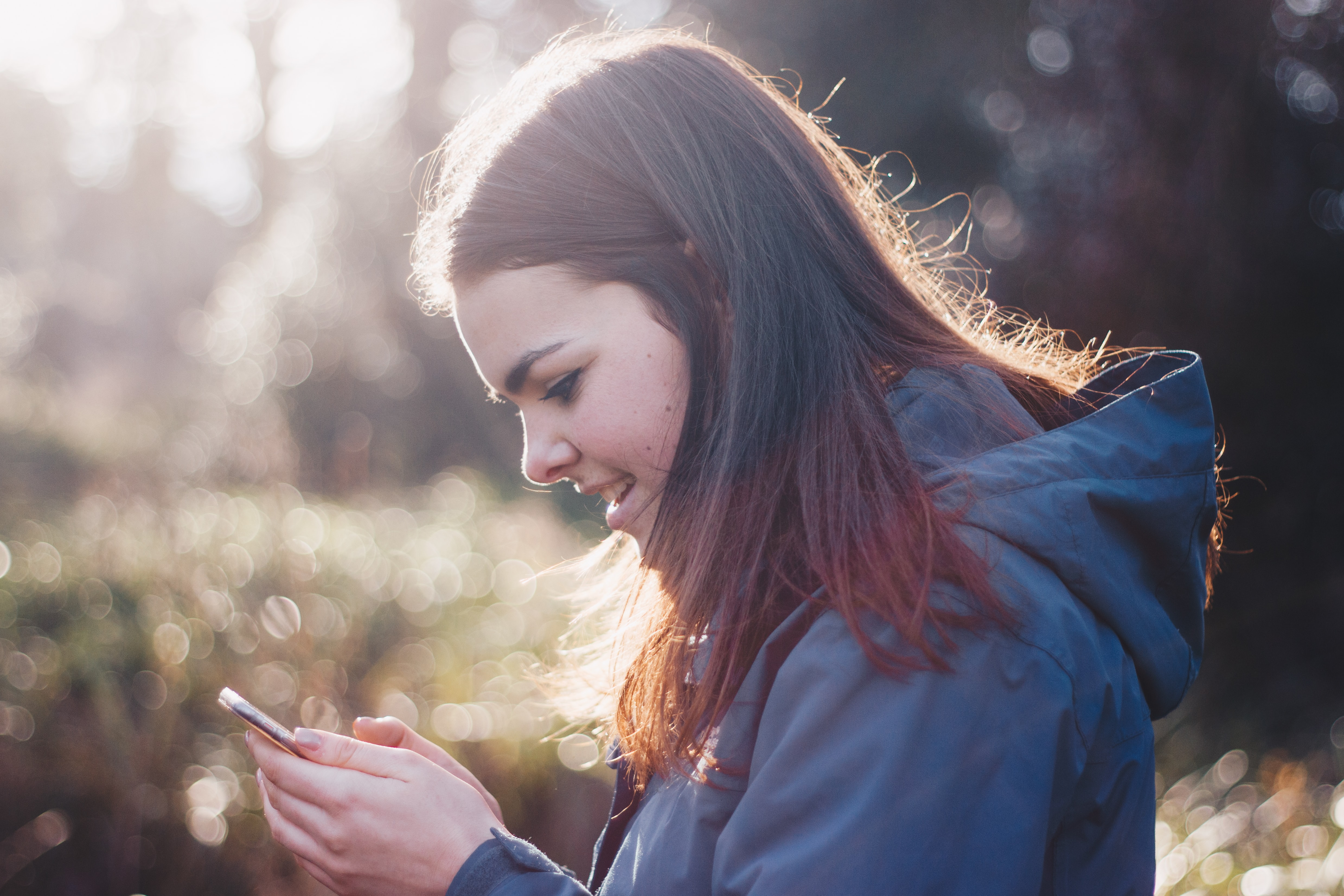A young woman smiling while looking at a smartphone
