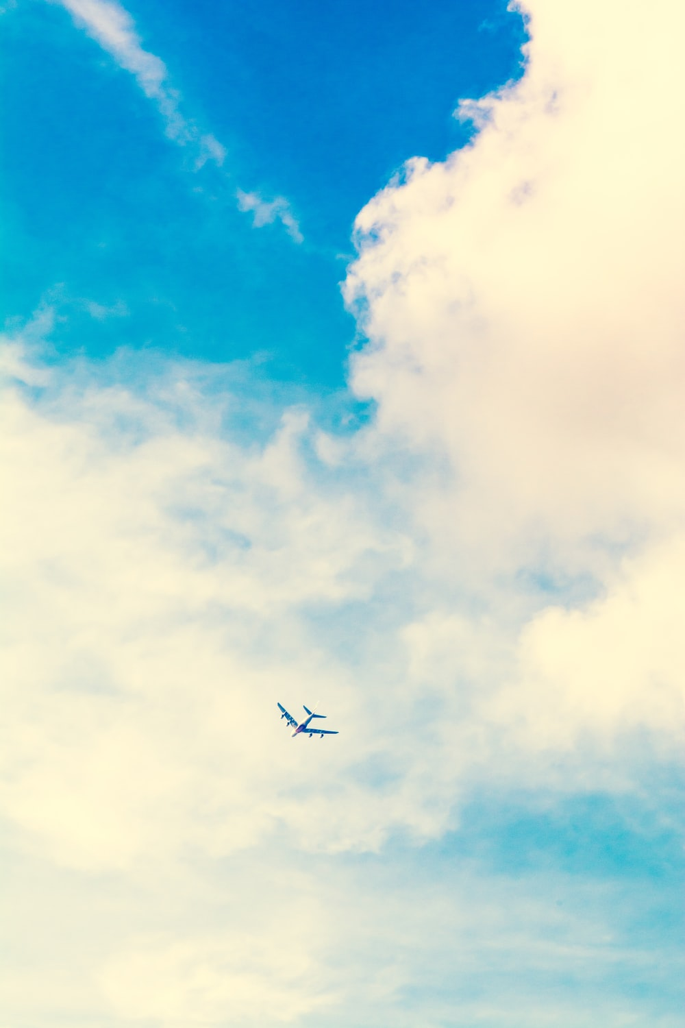 low angle photo of airplane and white clouds during daytime