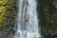 man hanging on rope near waterfalls during daytime