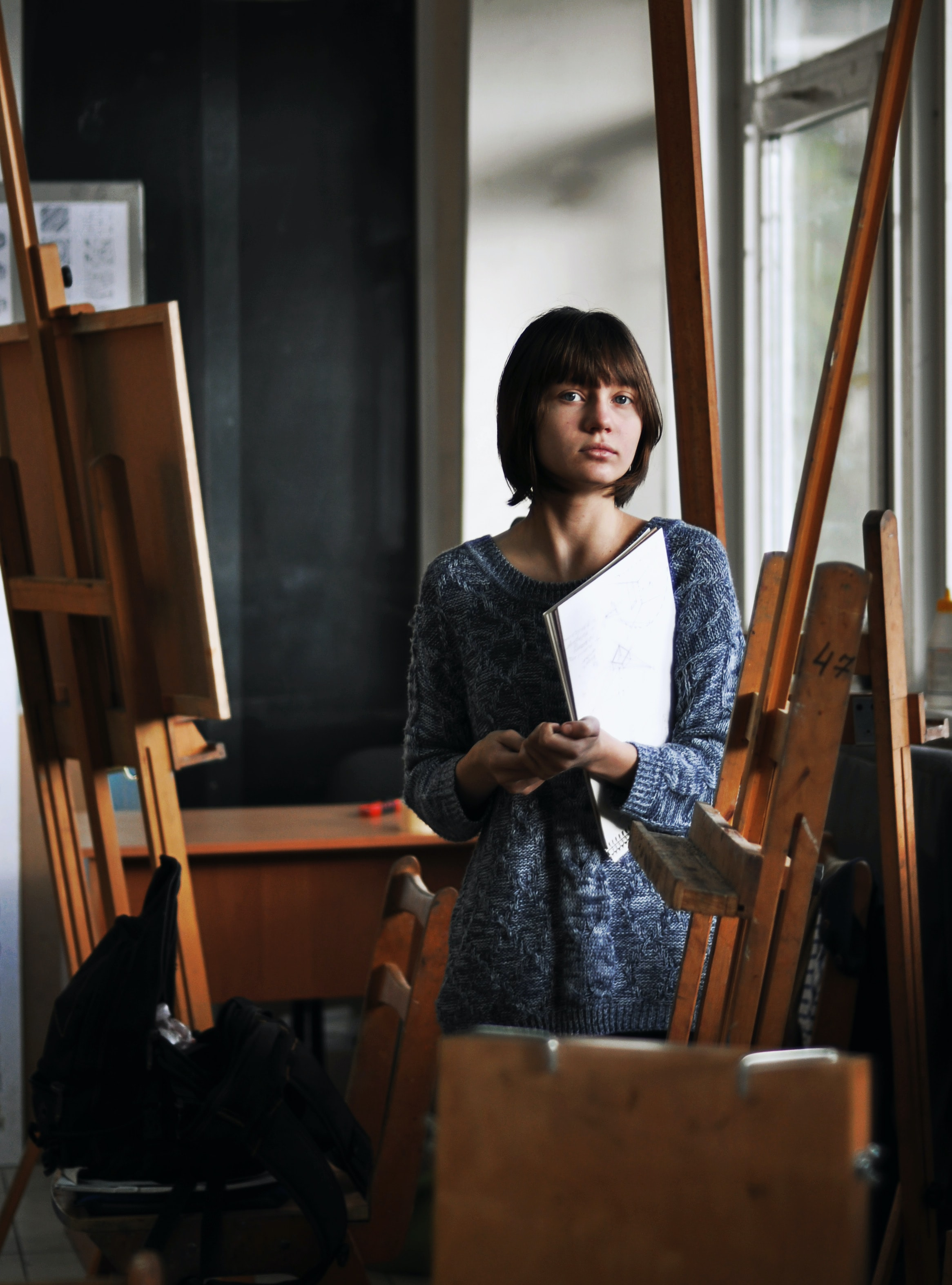 Artist stands alone in her studio with easels
