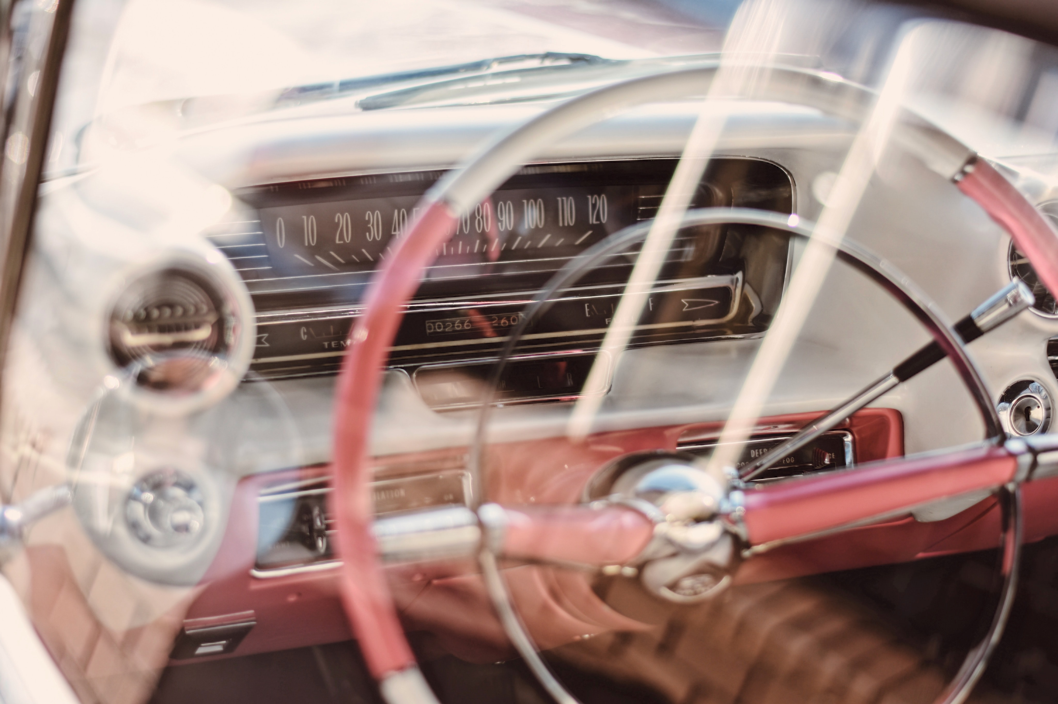 The steering wheel and dashboard inside an older car.