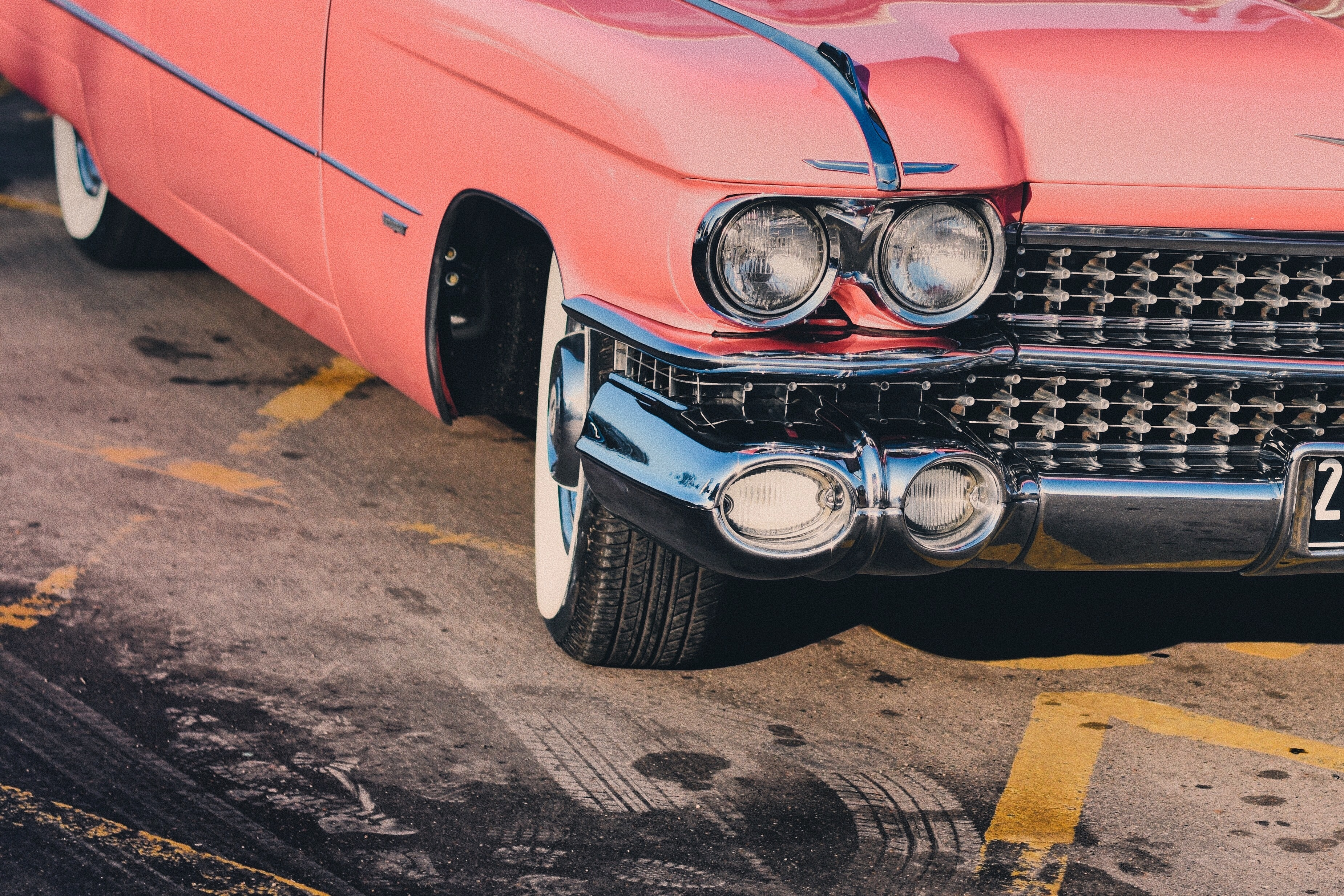 A shot of the front right view of a classic pink Chevrolet behind the skid marks.