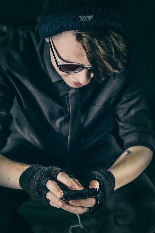 man wearing black top using smartphone