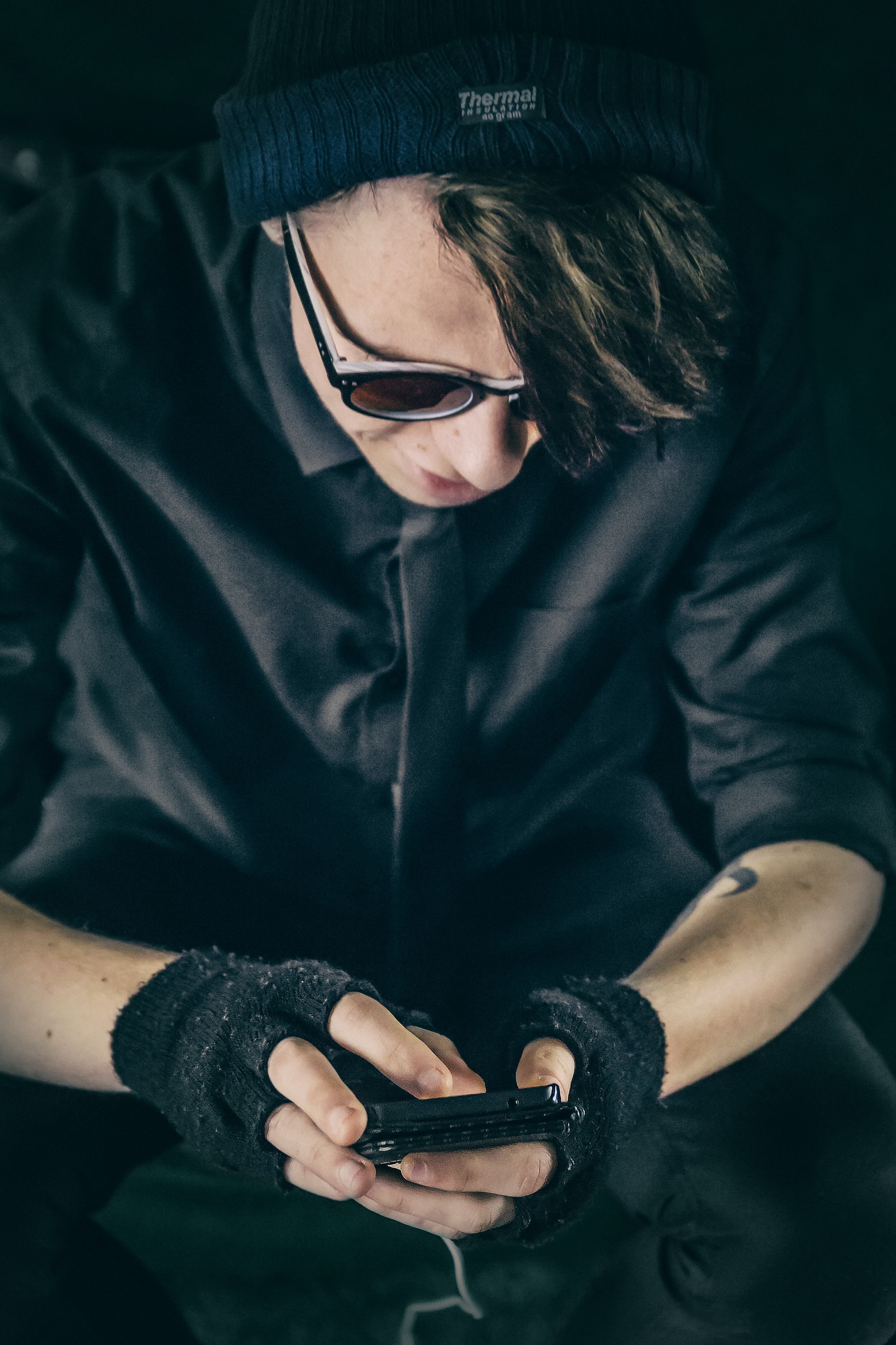 A person in black clothing and fingerless gloves looks down, using an iPhone