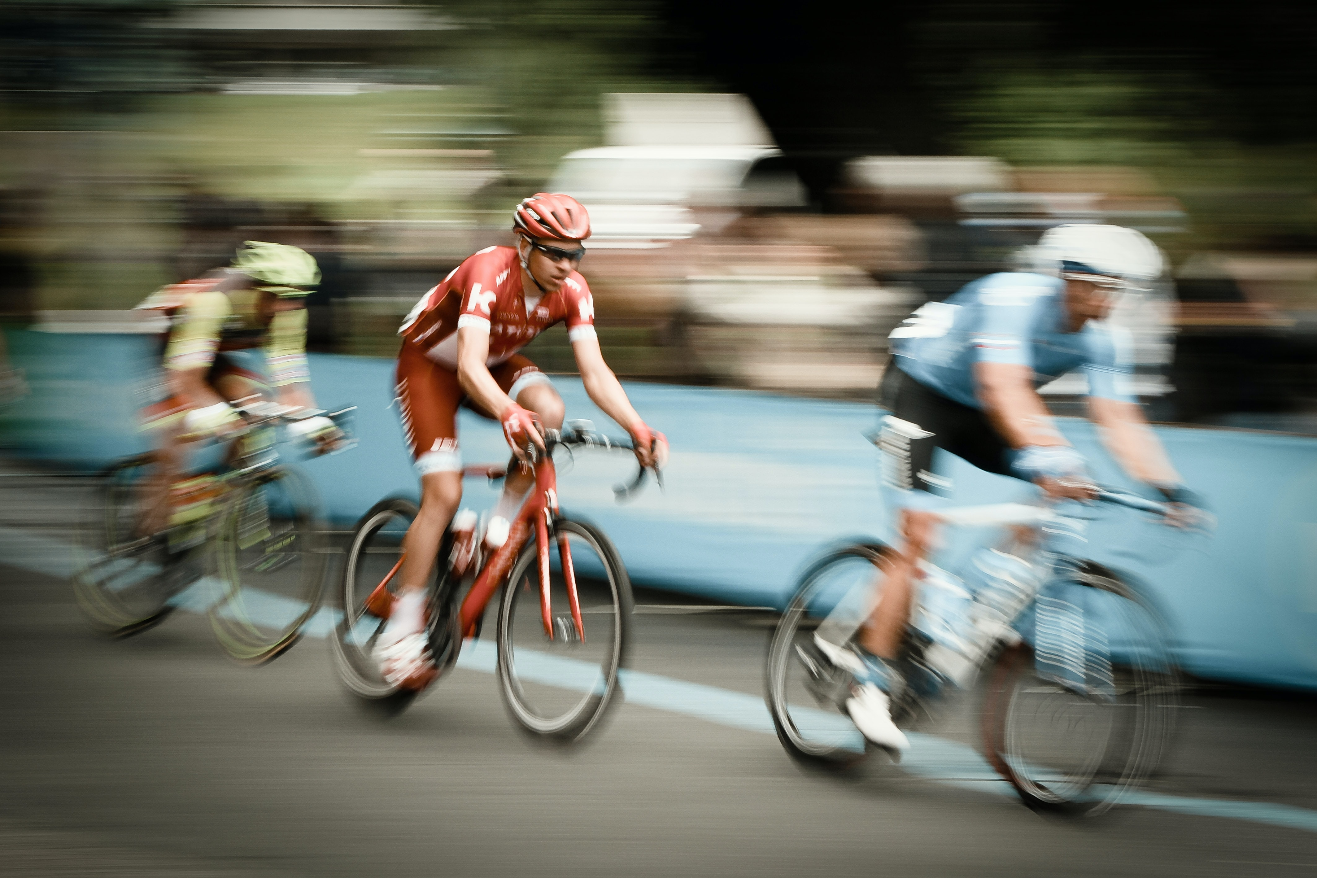 Three cyclists travel through Metropolitan City of Turin in the middle of a bike race