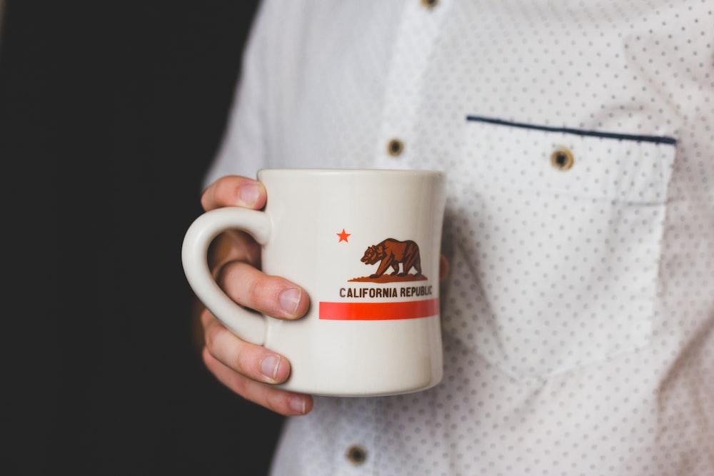 person holding white and red California Republic ceramic mug