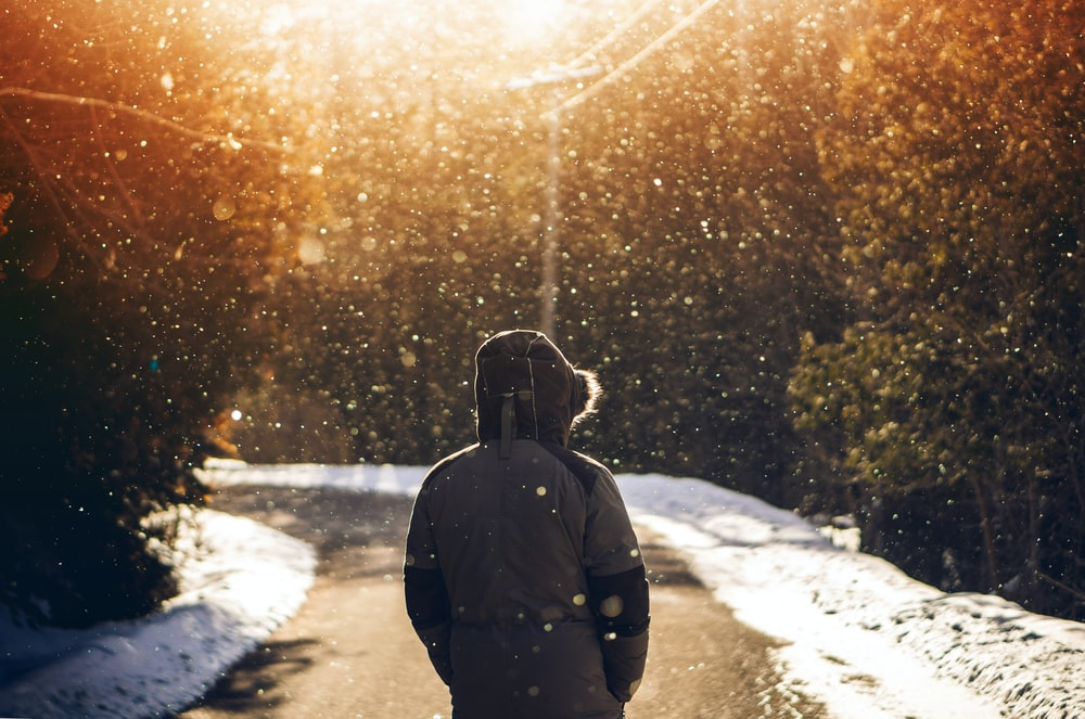 person wearing hoodie standing in middle of road with falling snow