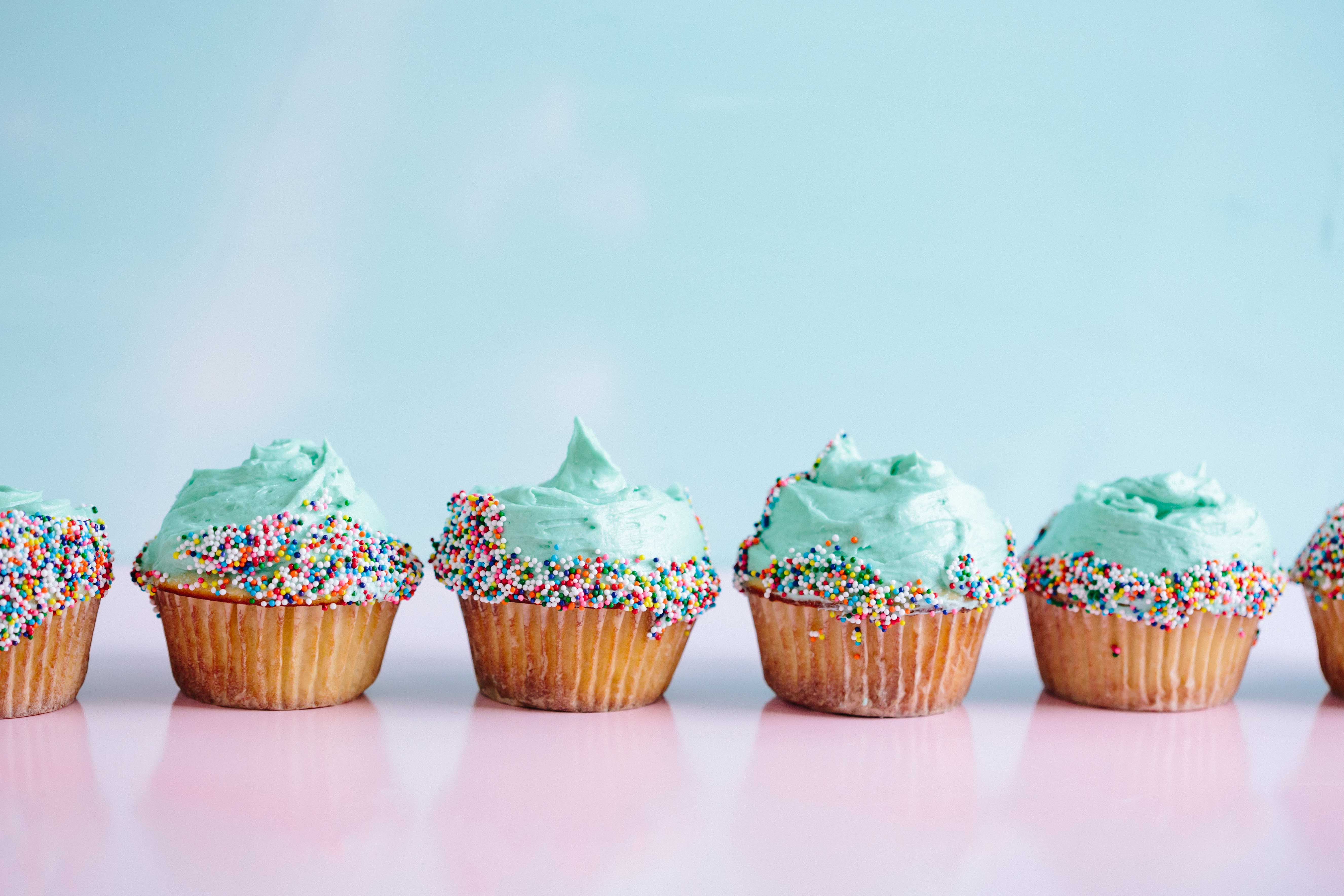 Row of cupcakes decorated with blue frosting and rainbow sprinkles