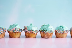 six teal icing cupcakes with sprinkles