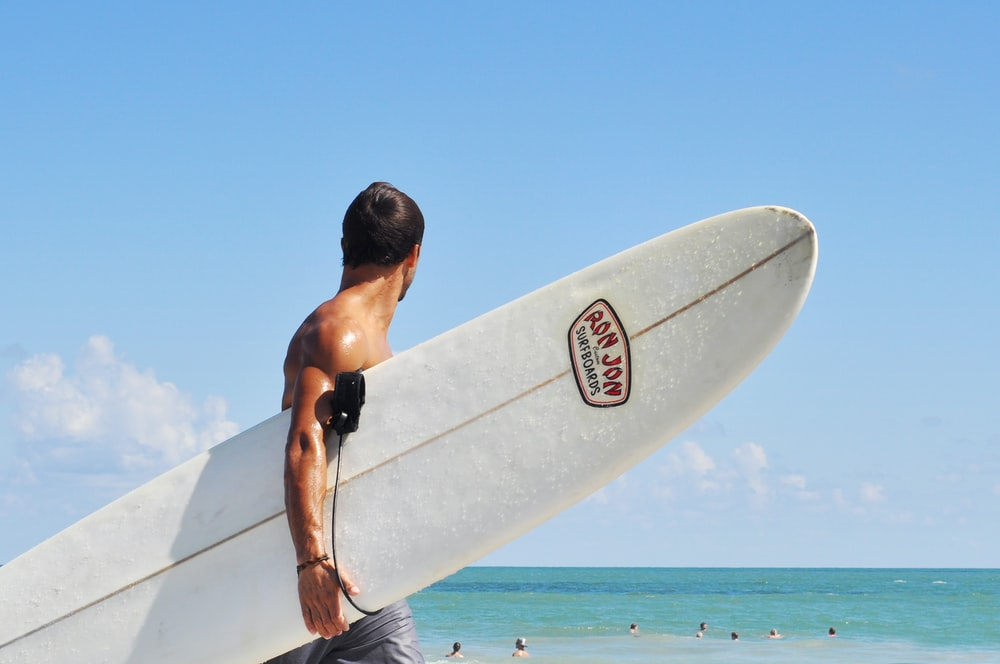 topless man carrying white surfboard in beach during daytime