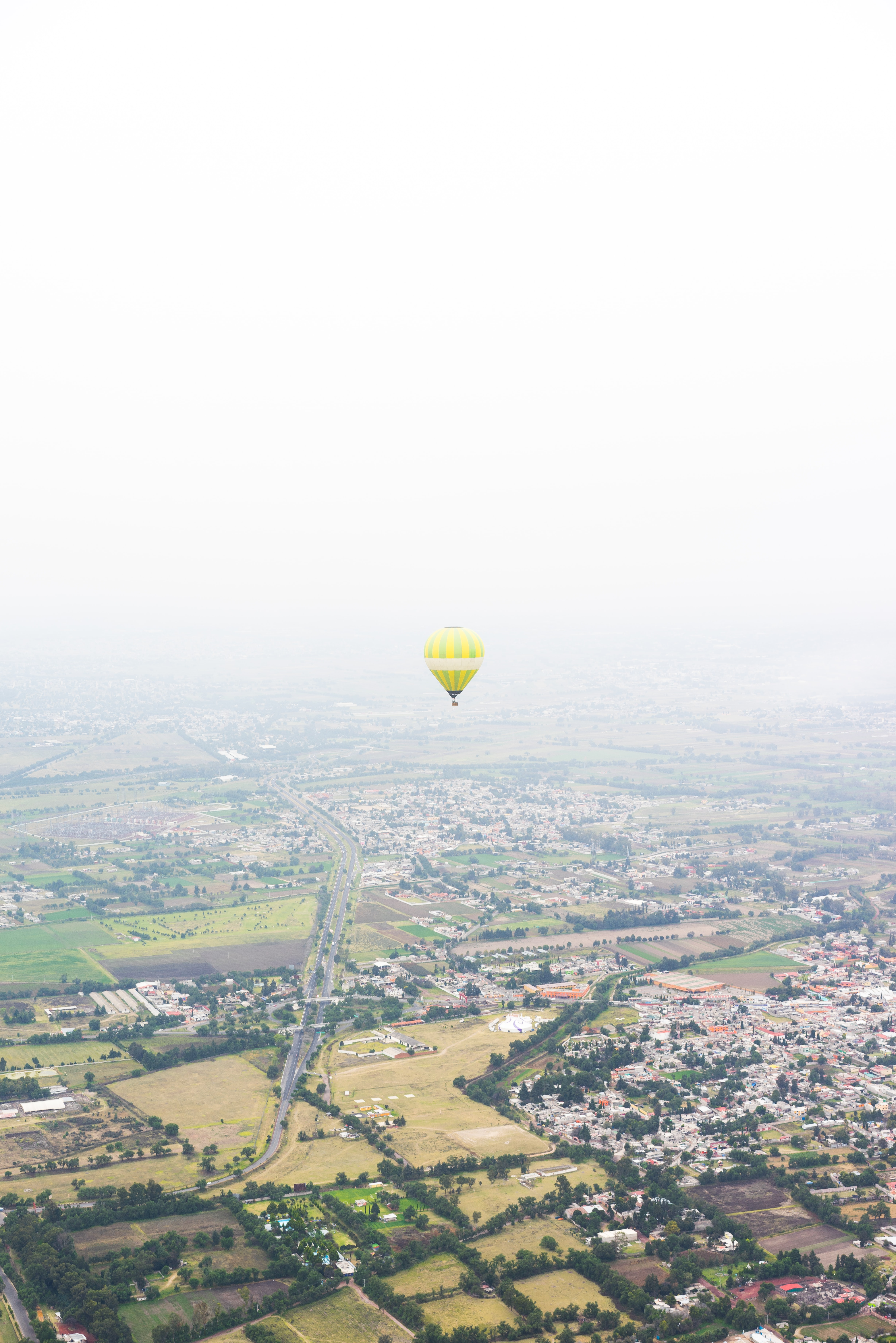 photo of yellow hot air balloon floating above houses