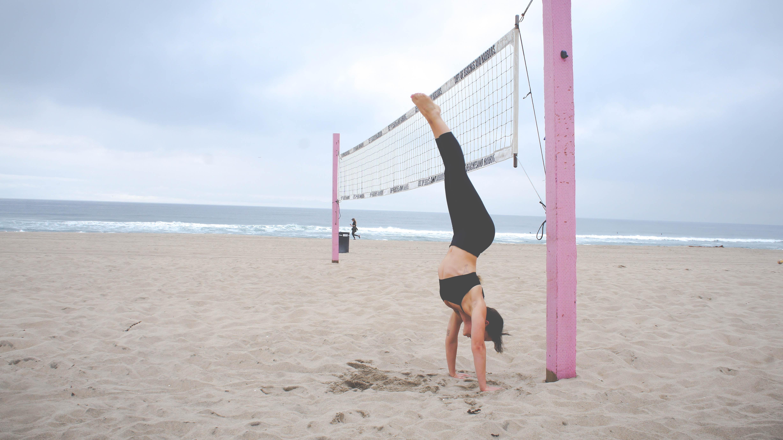 A woman doing a handstand next to a beach volleyball net.
