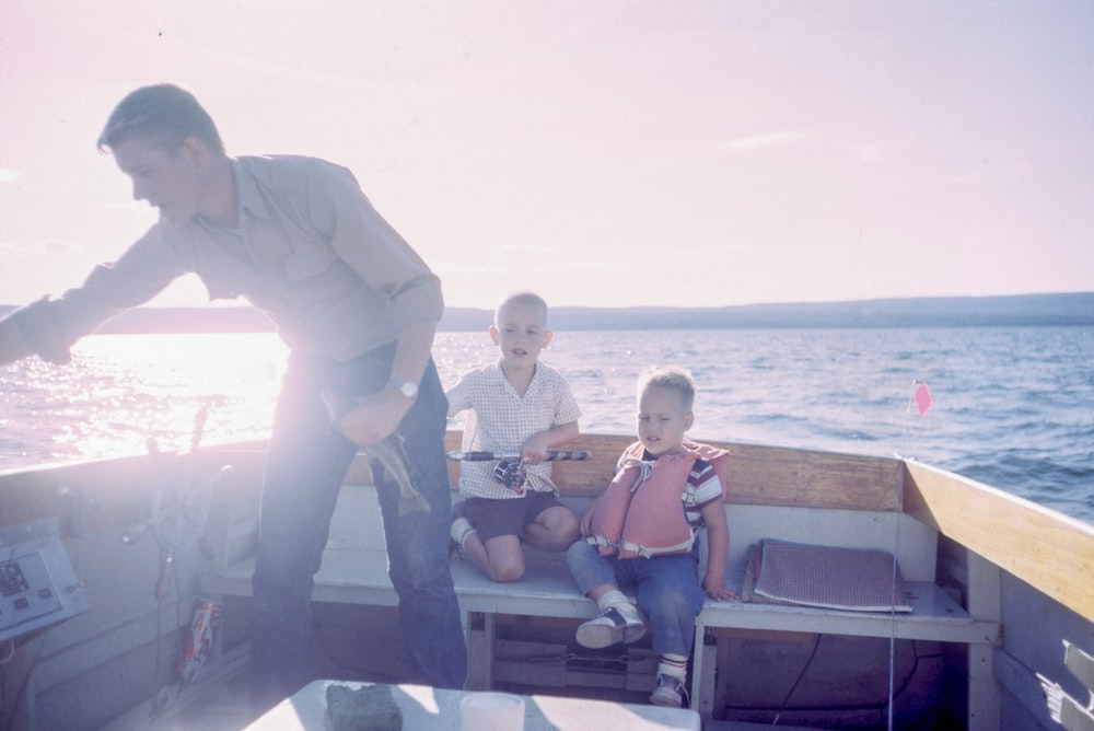 man holding gray fish standing beside two boys sitting on boat seats