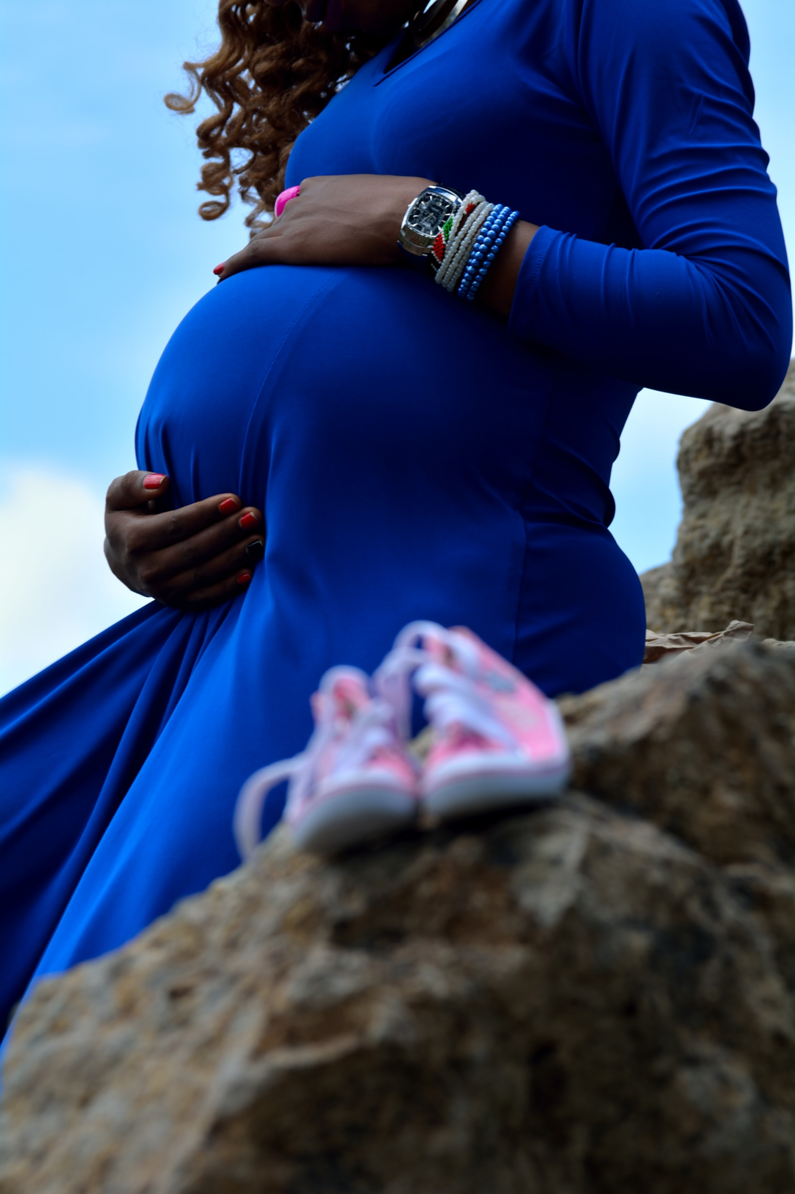 A pregnant woman's belly in a blue maternity dress.