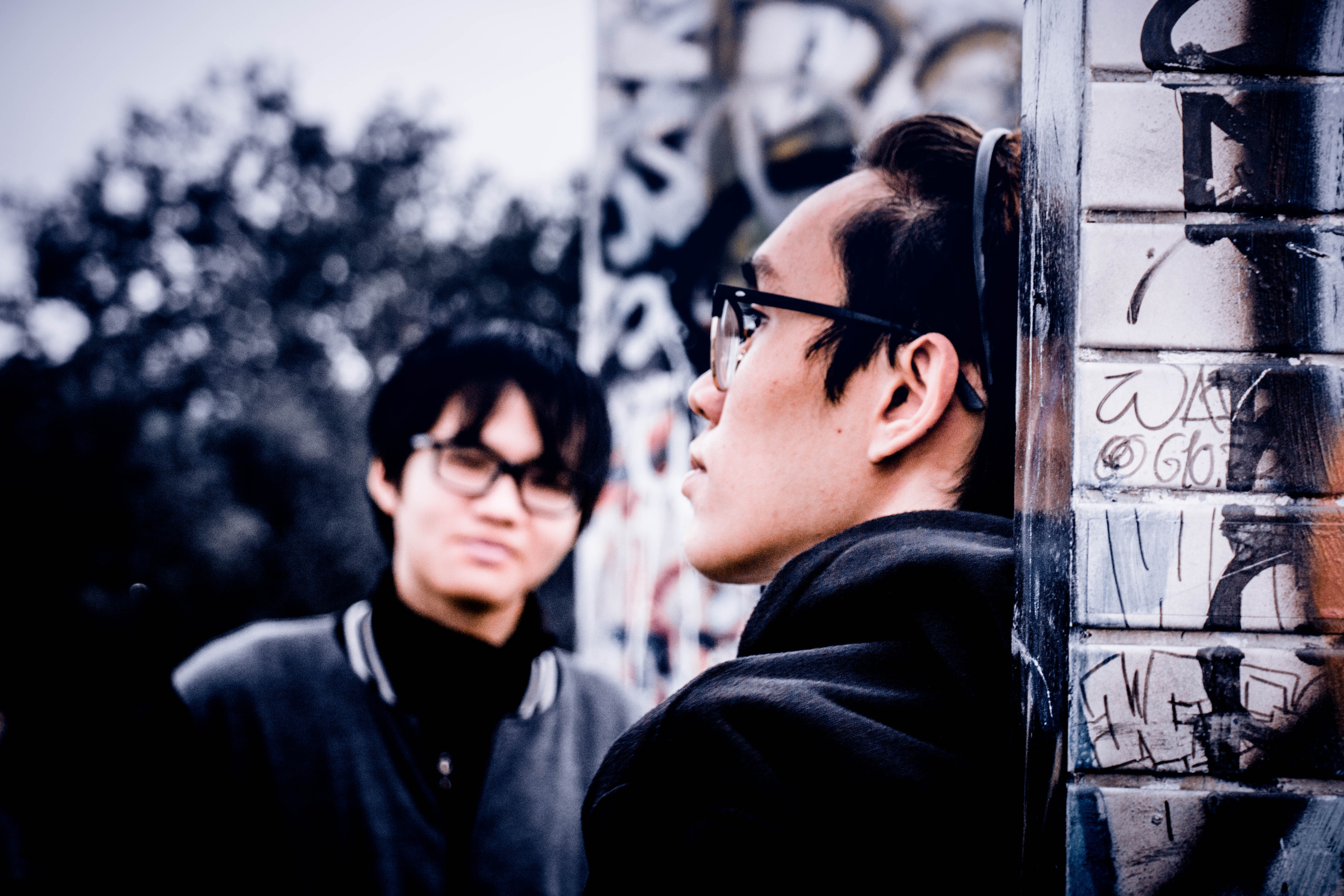 Two people in glasses stand, facing one another, against a graffitied brick wall