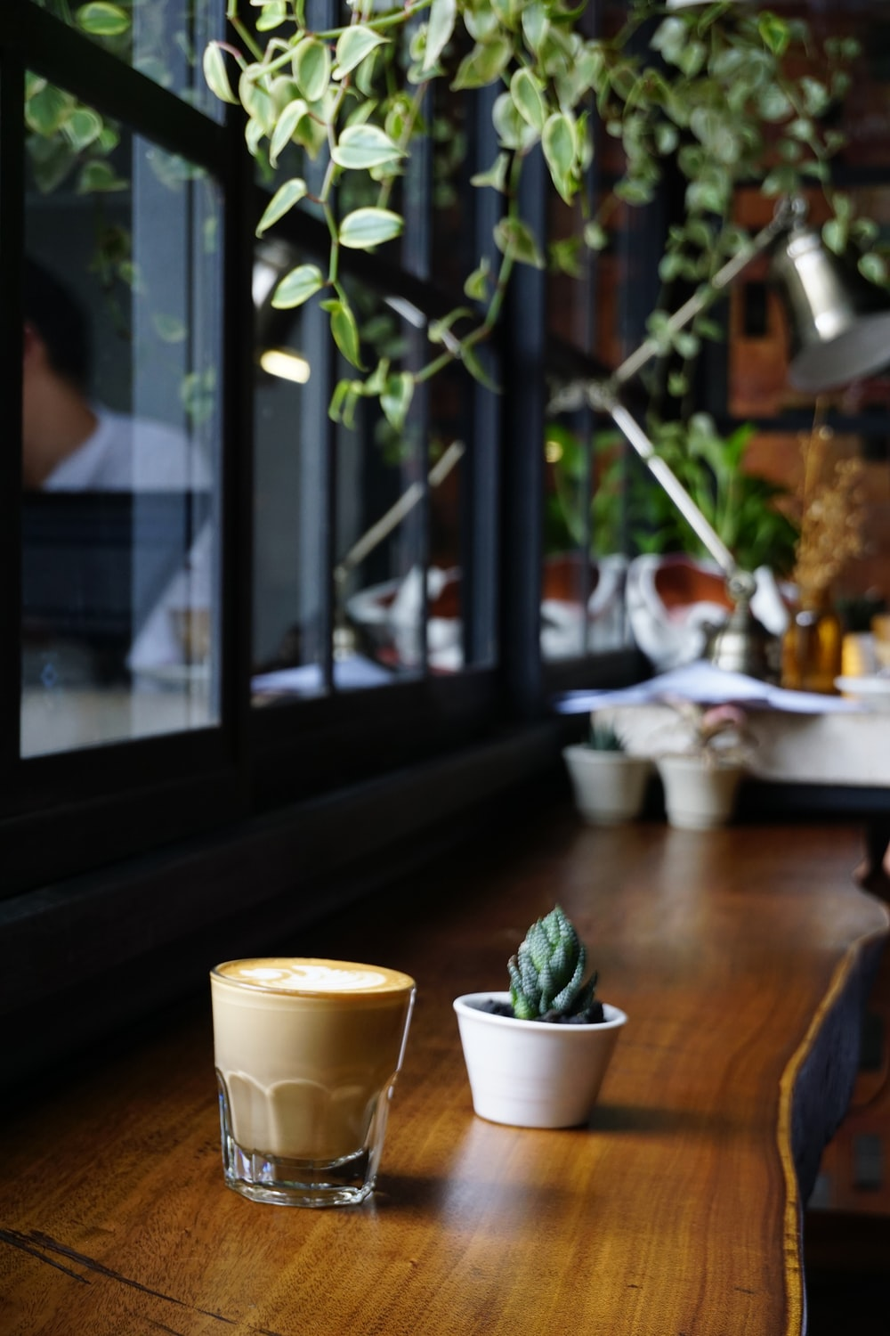 latte and cactus on brown wooden table
