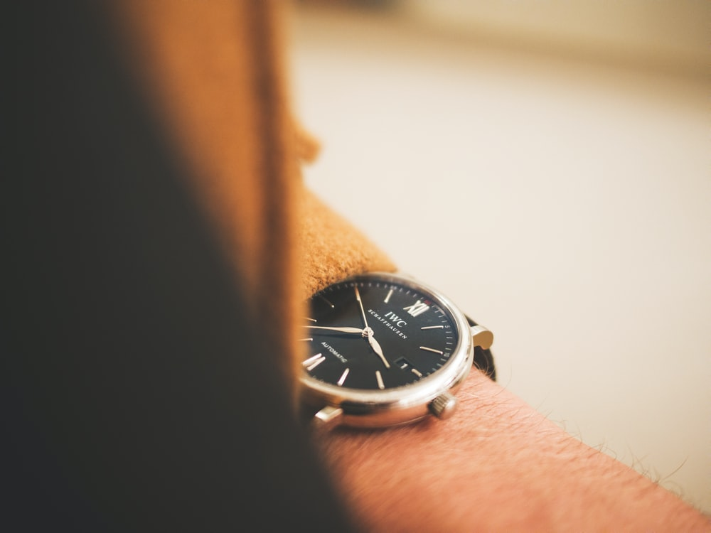 person holding round silver analog watch