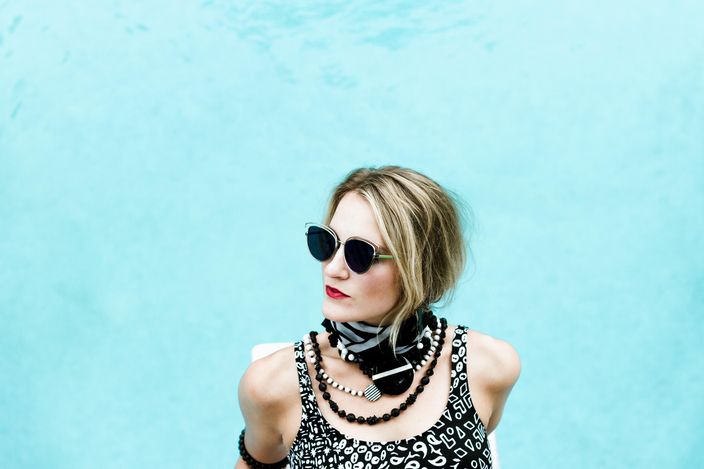 woman wearing sunglasses near blue surface