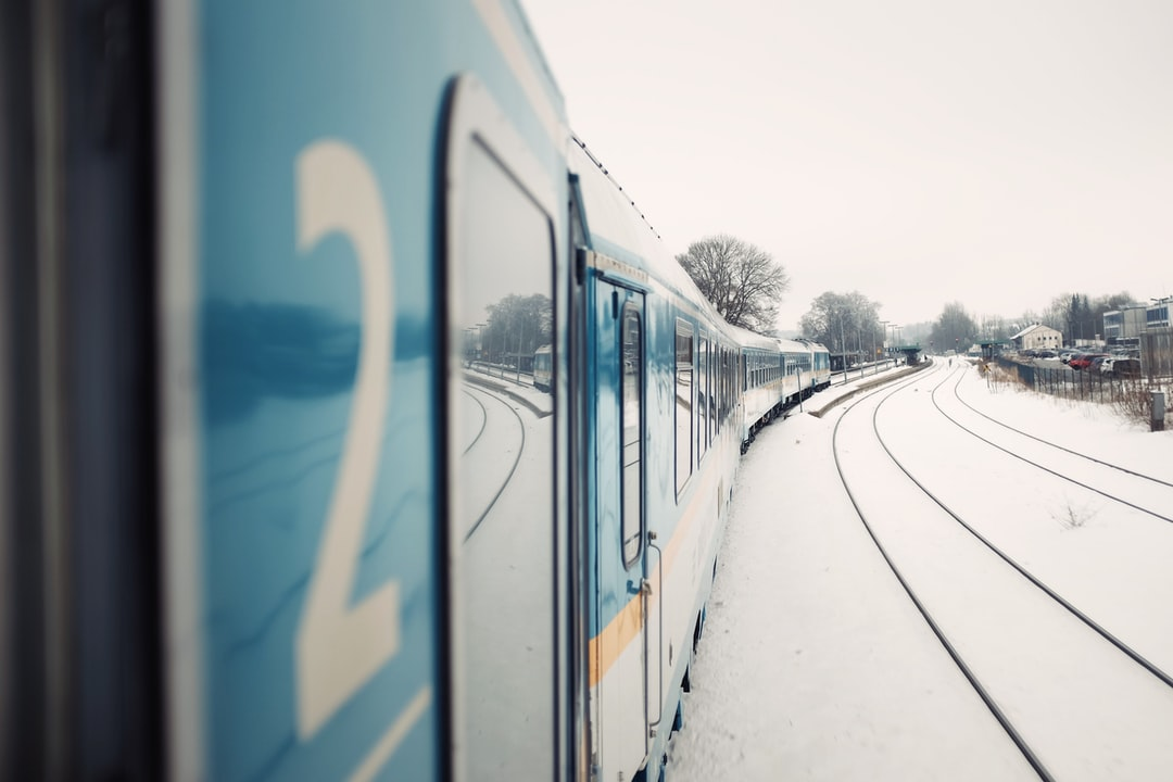 The railway tracks covered in snow as seen from the side of the train.