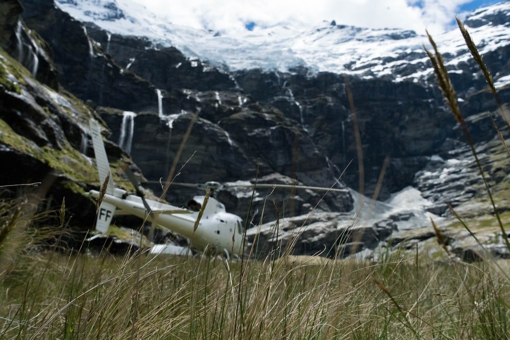 white helicopter near the snow capped mountains