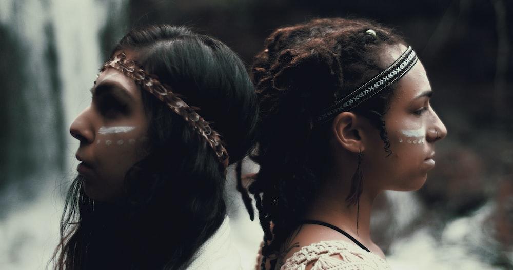 closeup photo of two women wearing headbands