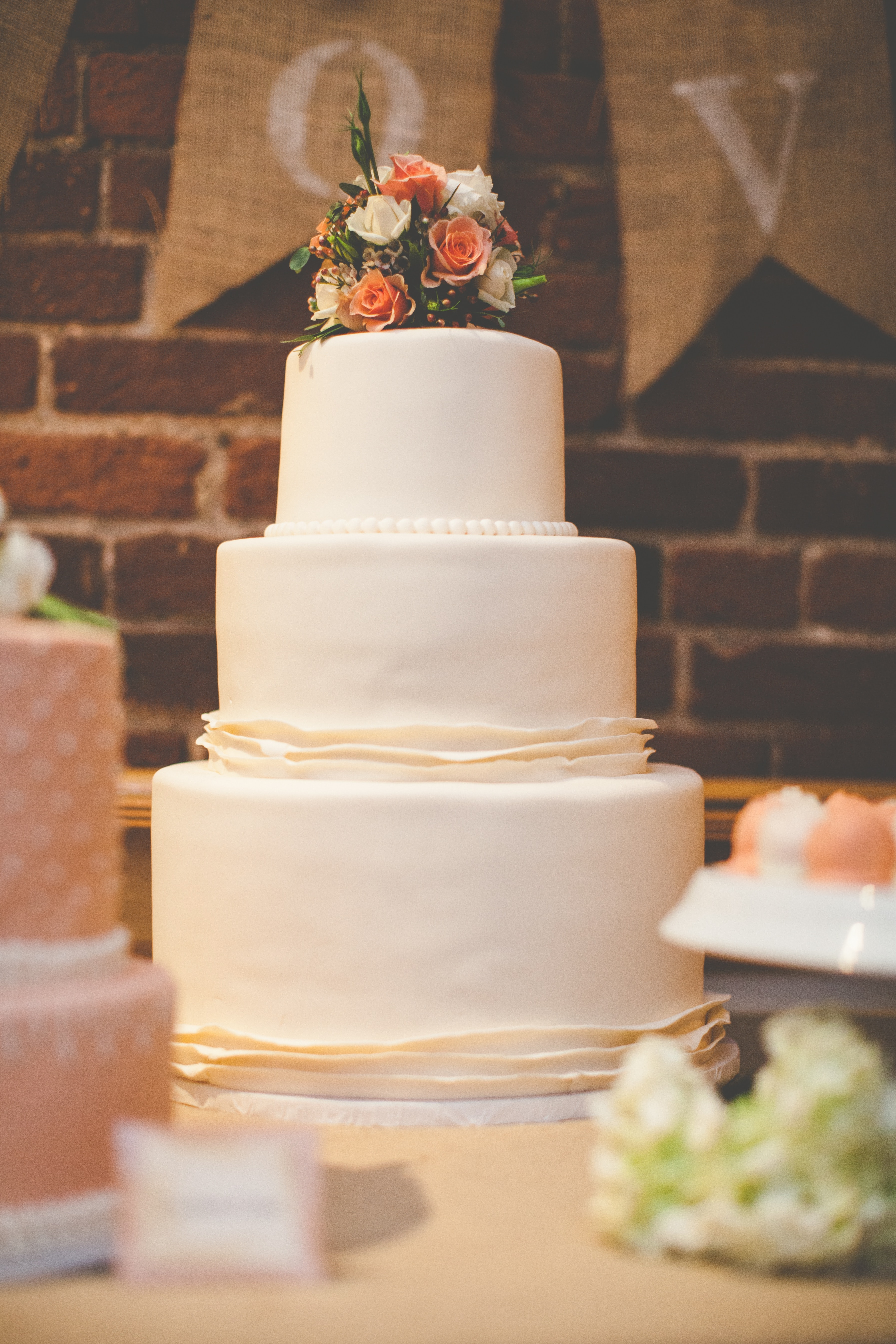 Three tier wedding cake in front of brick wall Noblesville