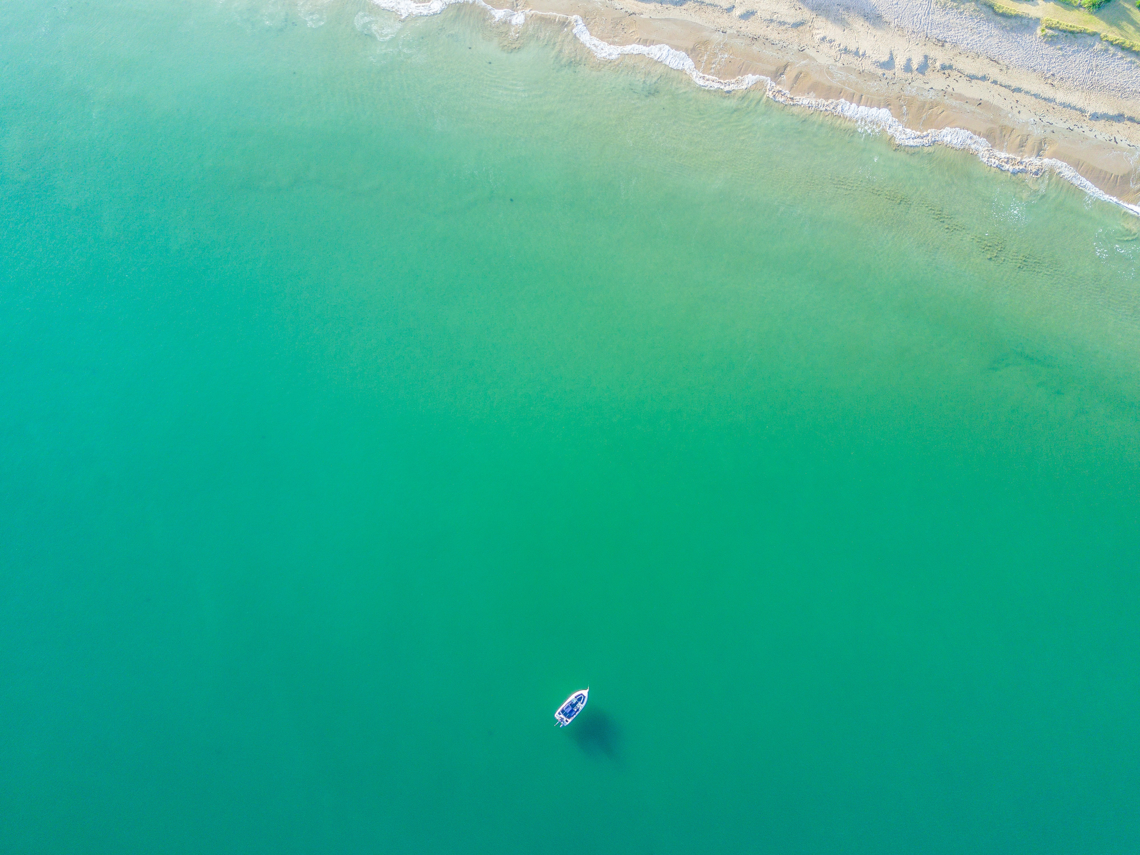 Drone aerial view of a boat in the green ocean at Te Ngaere
