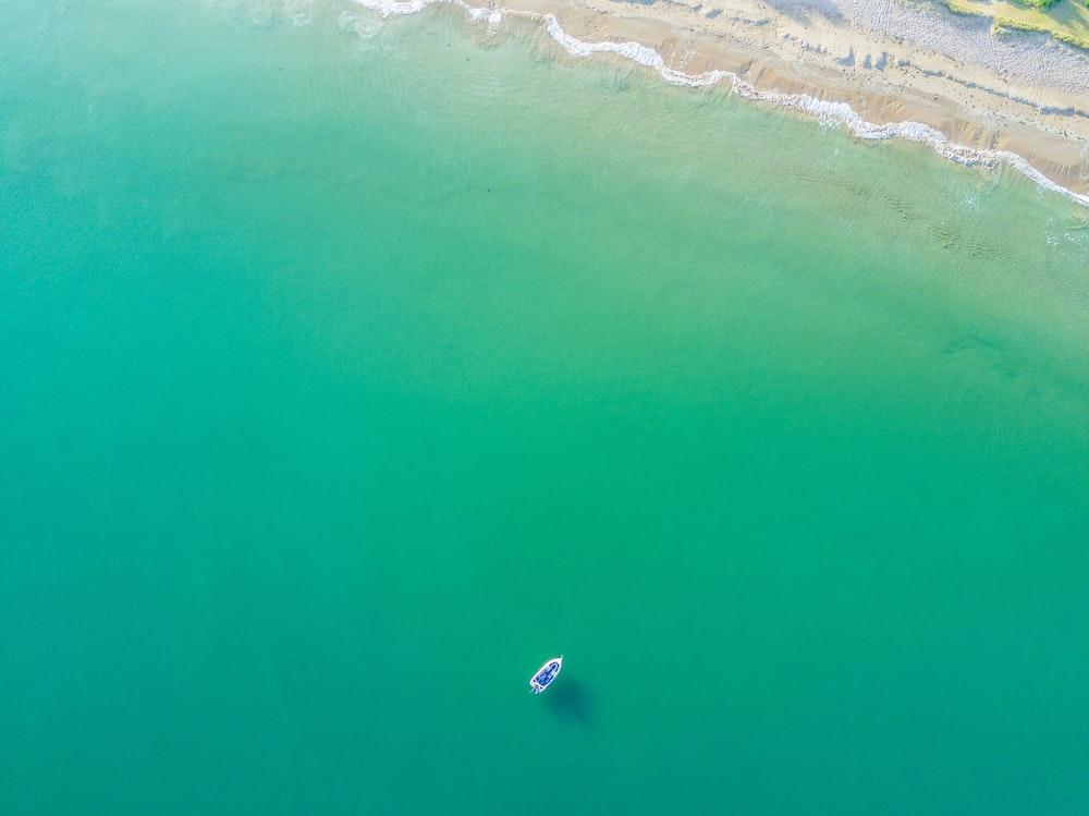 aerial photography of white boat on green ocean near seashore